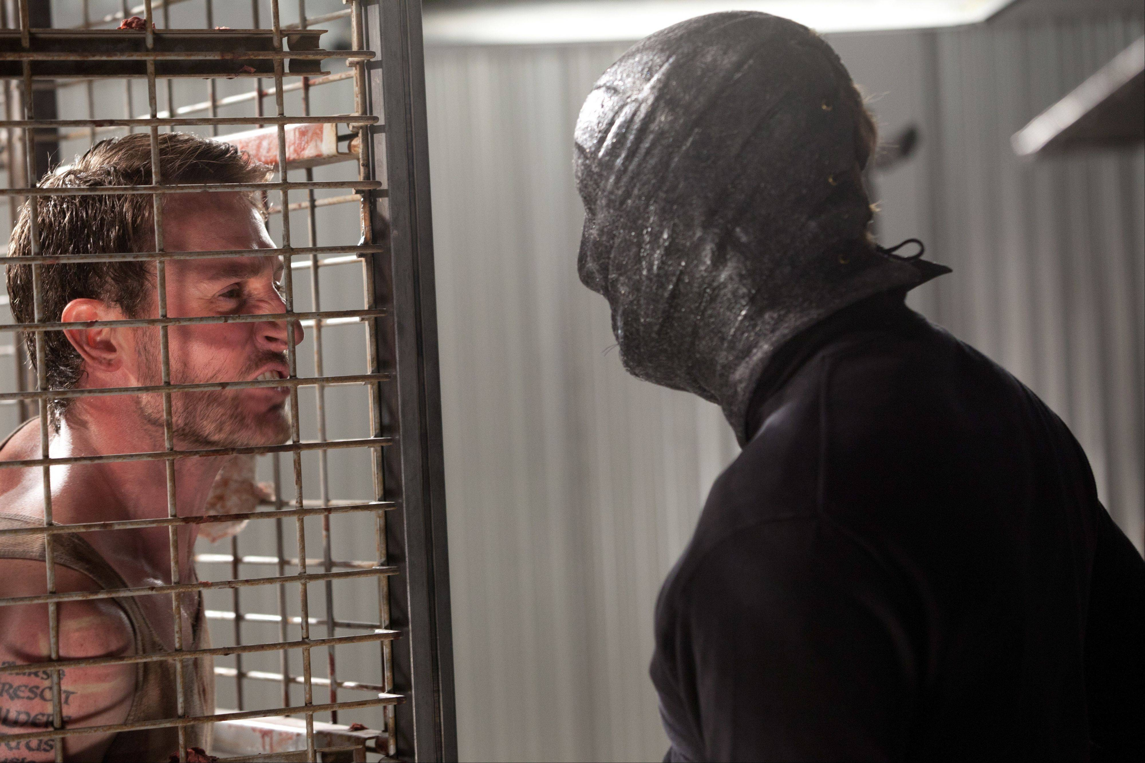 "A mysterious collector taunts one of his prisoners (Josh Stewart) in the horror film ""The Collection."""