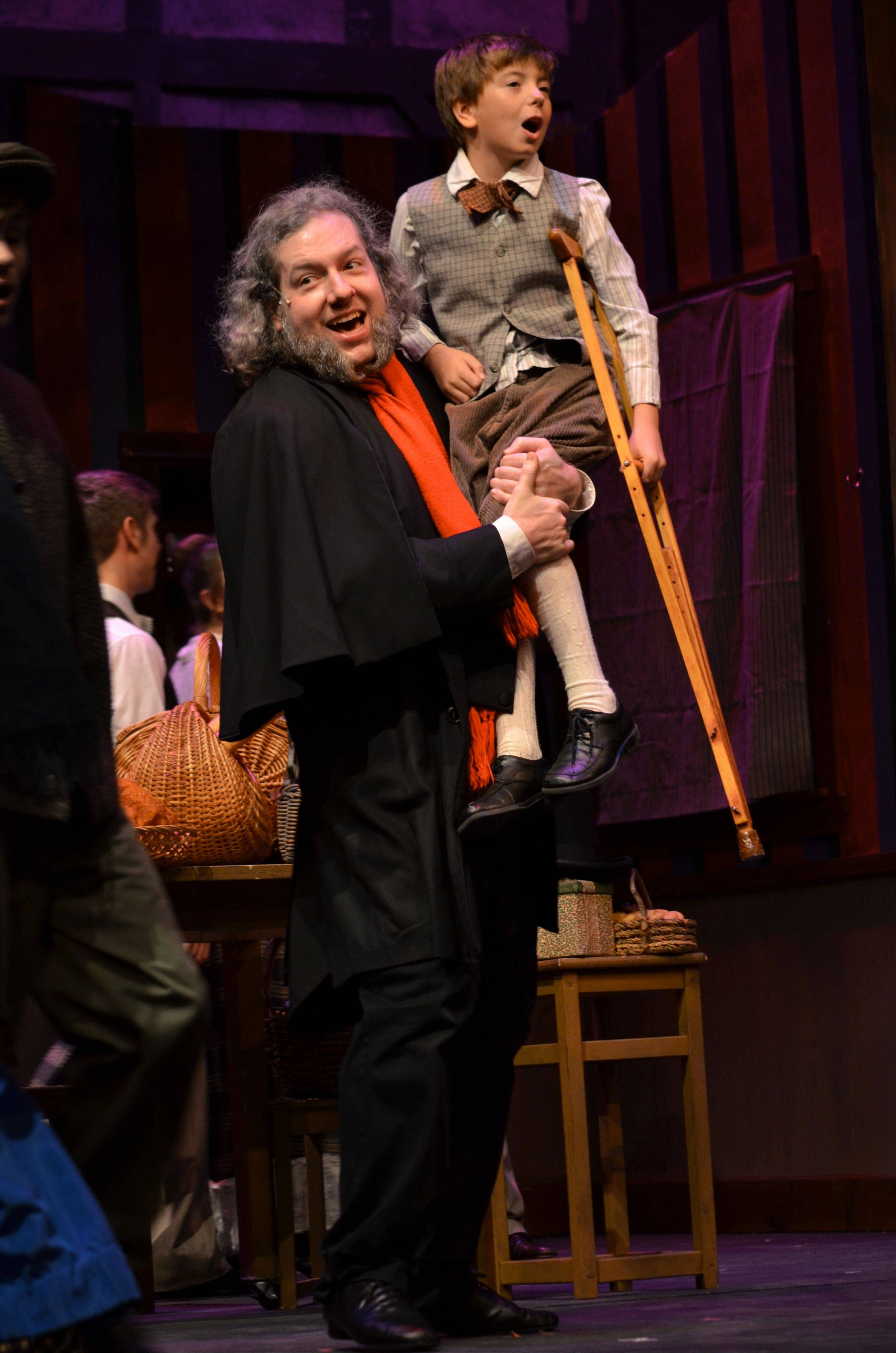 "Joshua K. Harris stars as Ebenezer Scrooge and Tyler Bednar is one of several youngsters playing Tiny Tim in the Metropolis Performing Arts Centre's 10th annual production of Charles Dickens' ""A Christmas Carol."""
