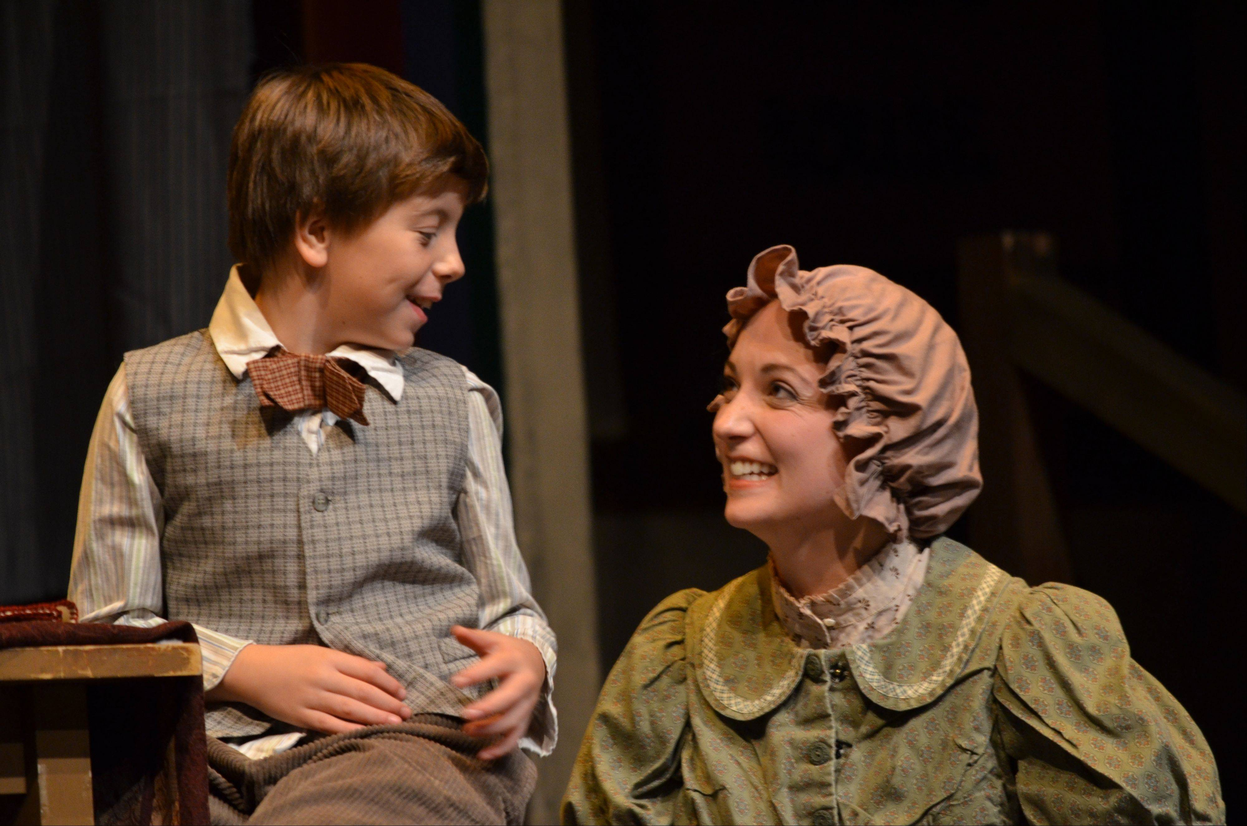 "Mrs. Cratchit (Megan M. Storti) makes merry with her youngest son, Tim (Tyler Bednar), in ""A Christmas Carol,"" a play with music running through Dec. 24 at the Metropolis Performing Arts Centre in Arlington Heights."