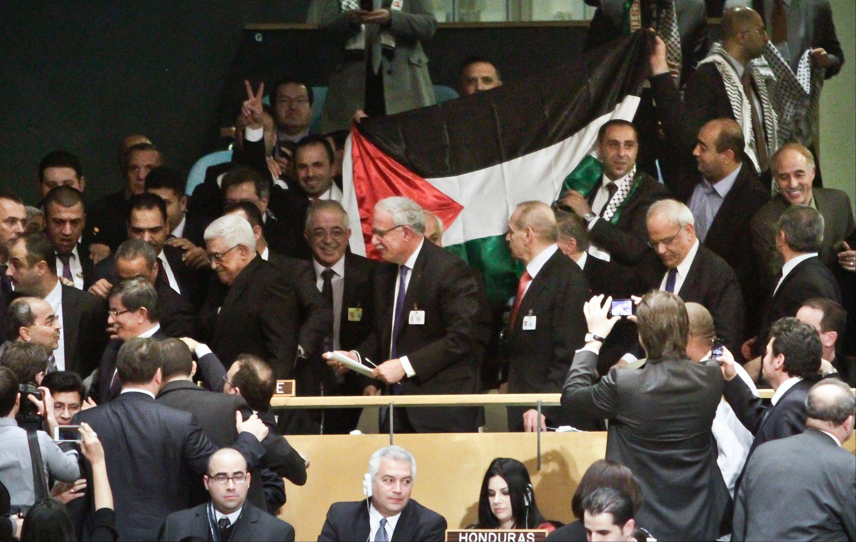 A Palestinian flag is displayed as Palestinian President Mahmoud Abbas leads his delegation from the U.N. General Assembly after a vote recognizing Palestine as a state on Thursday, Nov. 29, 2012 in New York. Palestinians won the statehood vote, even as the U.S., Israel's closest ally, mounted a campaign to head off the General Assembly vote.