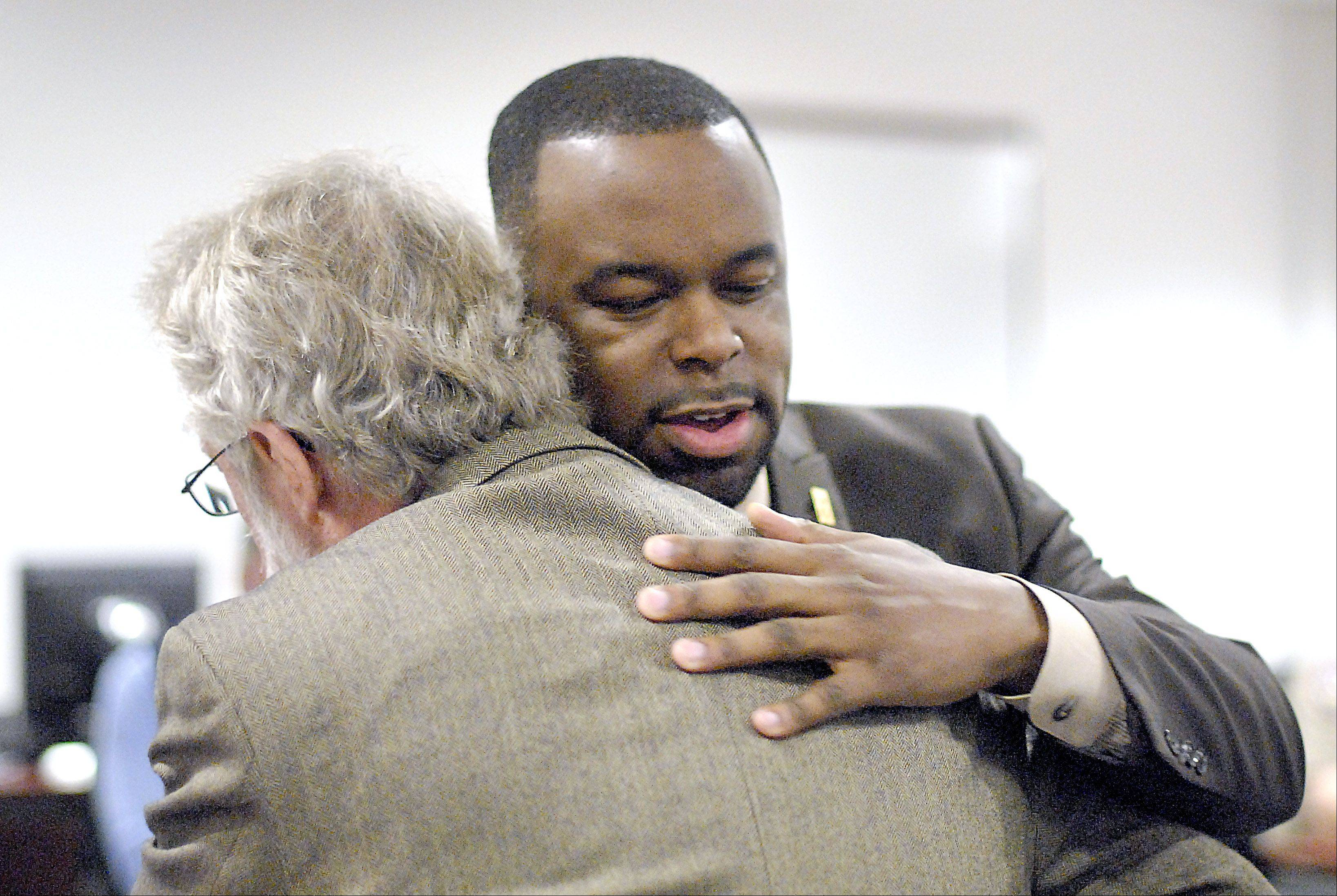 Clayton Muhammad, director of community relations for East Aurora School District 131, hugs Aurora Mayor Tom Weisner for nominating him for the 2012 Roscoe Ebey Award. Muhammad was named the award winner by Kane County Sheriff Pat Perez.
