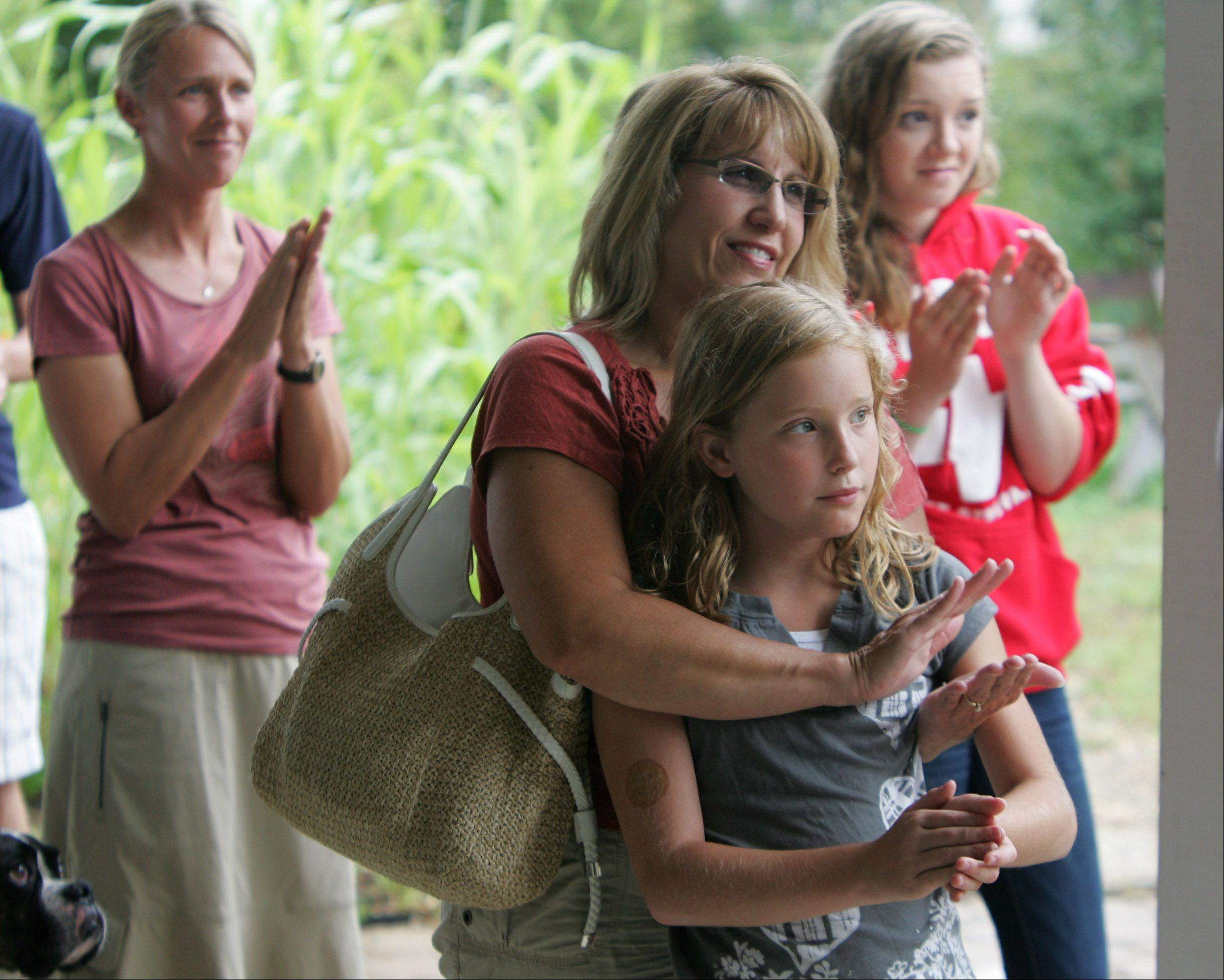 Cindy Batz of Gurnee and her daughter Amy, 10, join other supporters clapping for Abby Goldberg of Grayslake. Goldberg advocates giving communities more authority to ban plastic bags.