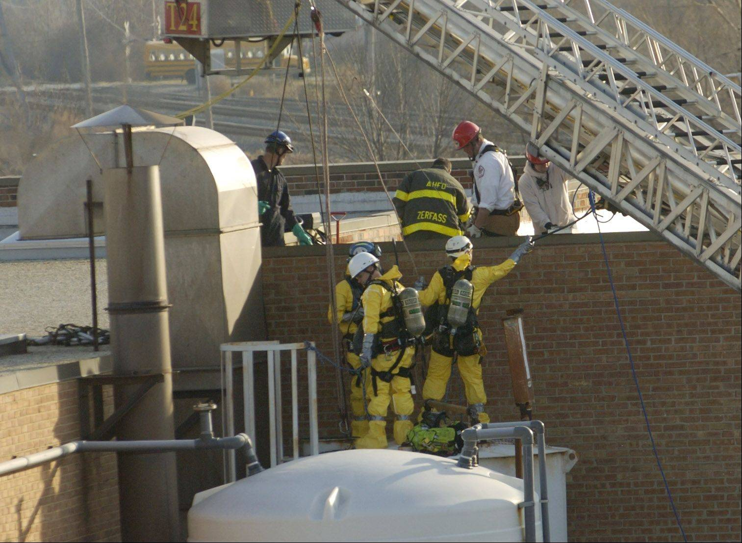 Rescue workers attempt to remove the body of a man who died in a chemical tank Thursday at a business in Wheeling.