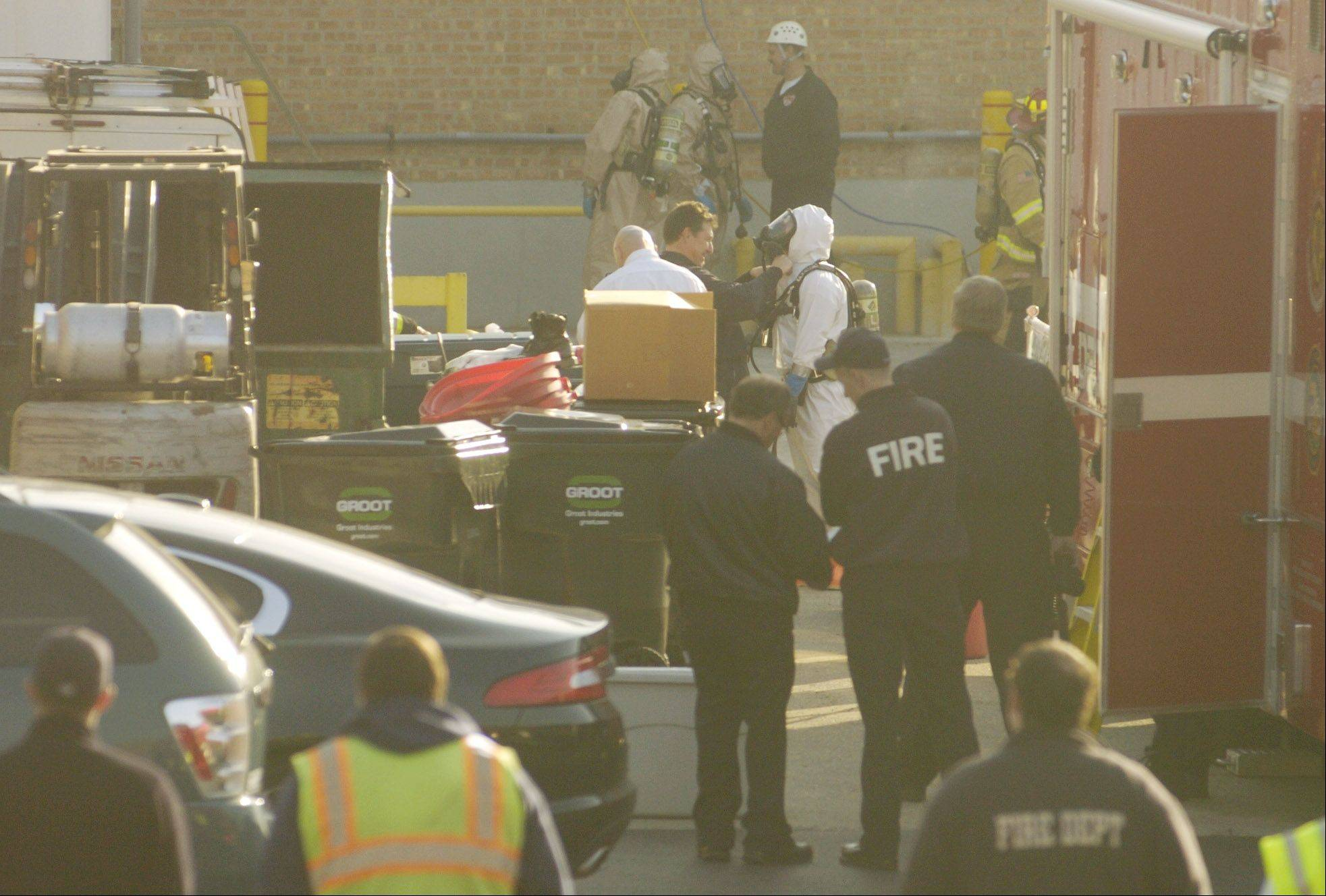 Rescue workers attempt to remove the body of a man who died in a chemical tank at a business in Wheeling.