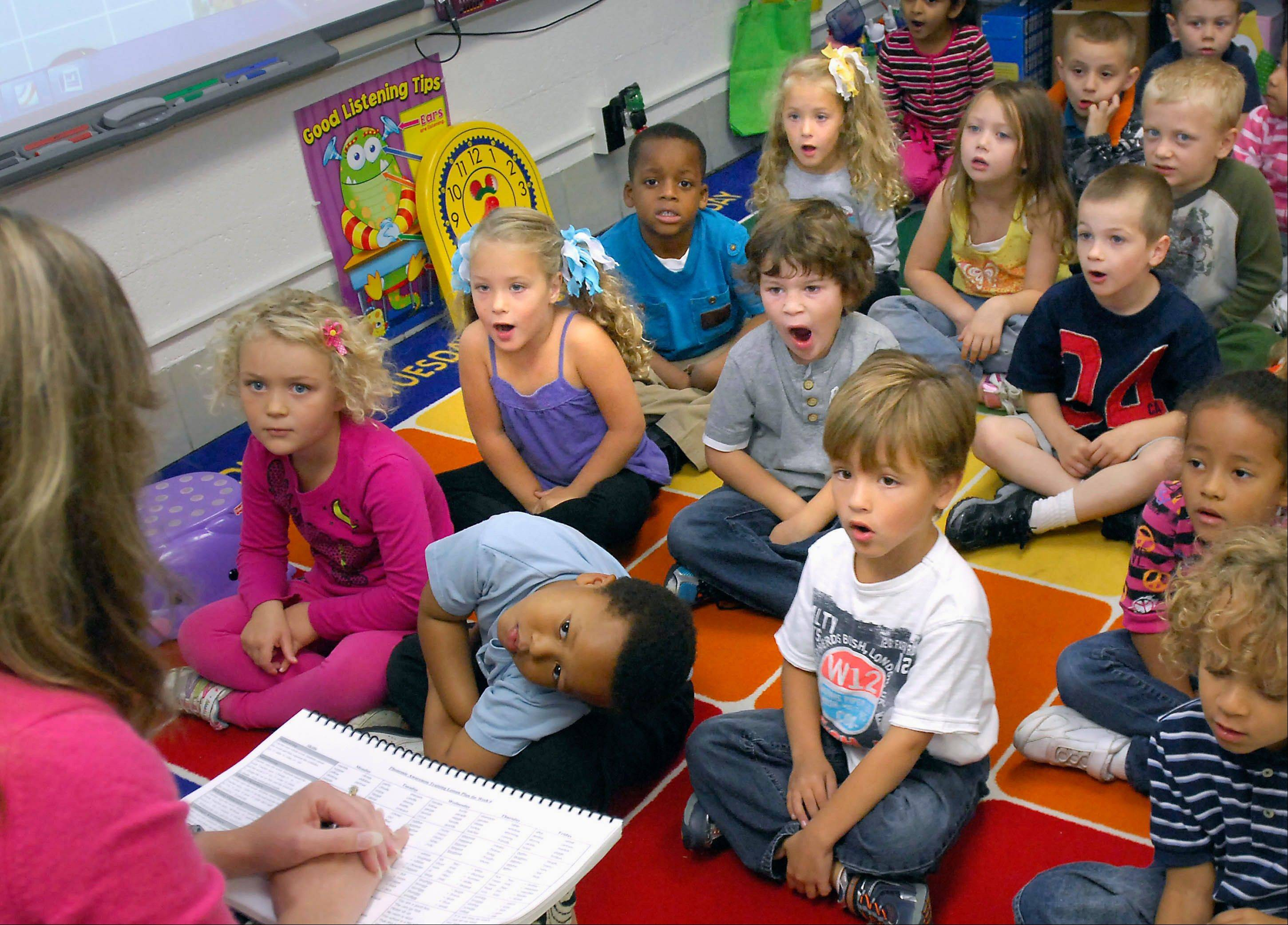 Five-year-old triplets Cameron Schirano, left, with blue and white bows, sister, Ella, with yellow and white bows, and brother, James, in foreground with white T-shirt, are split up during class to promote independence during a lesson with Oakland Elementary School teacher Anita Kirk in Bloomington.