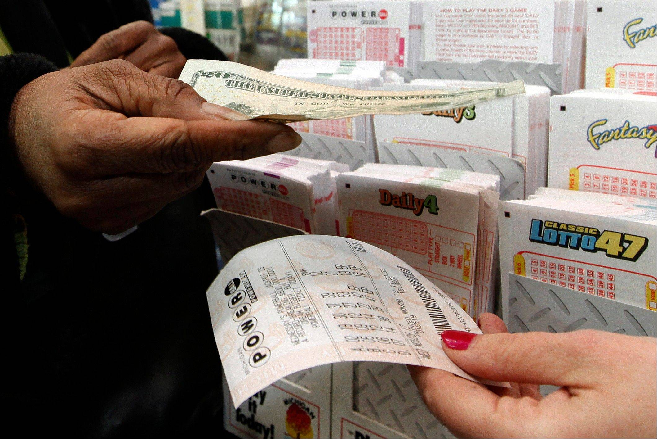 "Donna Fields pays for her Powerball tickets in Detroit yesterday. Fields picked two sets of numbers off the top of her head and two easy picks. Fields said, ""If I won I would take care of God first, then my family and do some traveling, and oh yeah, quit my job."""