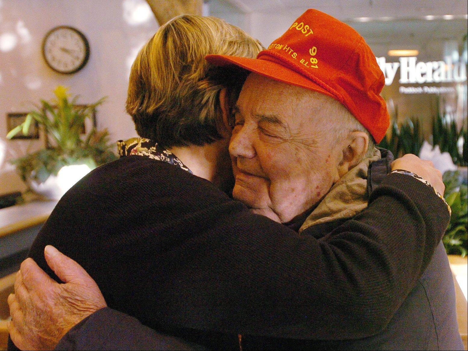 Touched by the kindness he received throughout his life, Walt Meder, 90, of Arlington Heights, hugs M. Eileen Brown, the Daily Herald's assistant vice president and director of strategic marketing and innovation, to celebrate the launching of a new charitable effort to provide holiday gifts to needy kids.