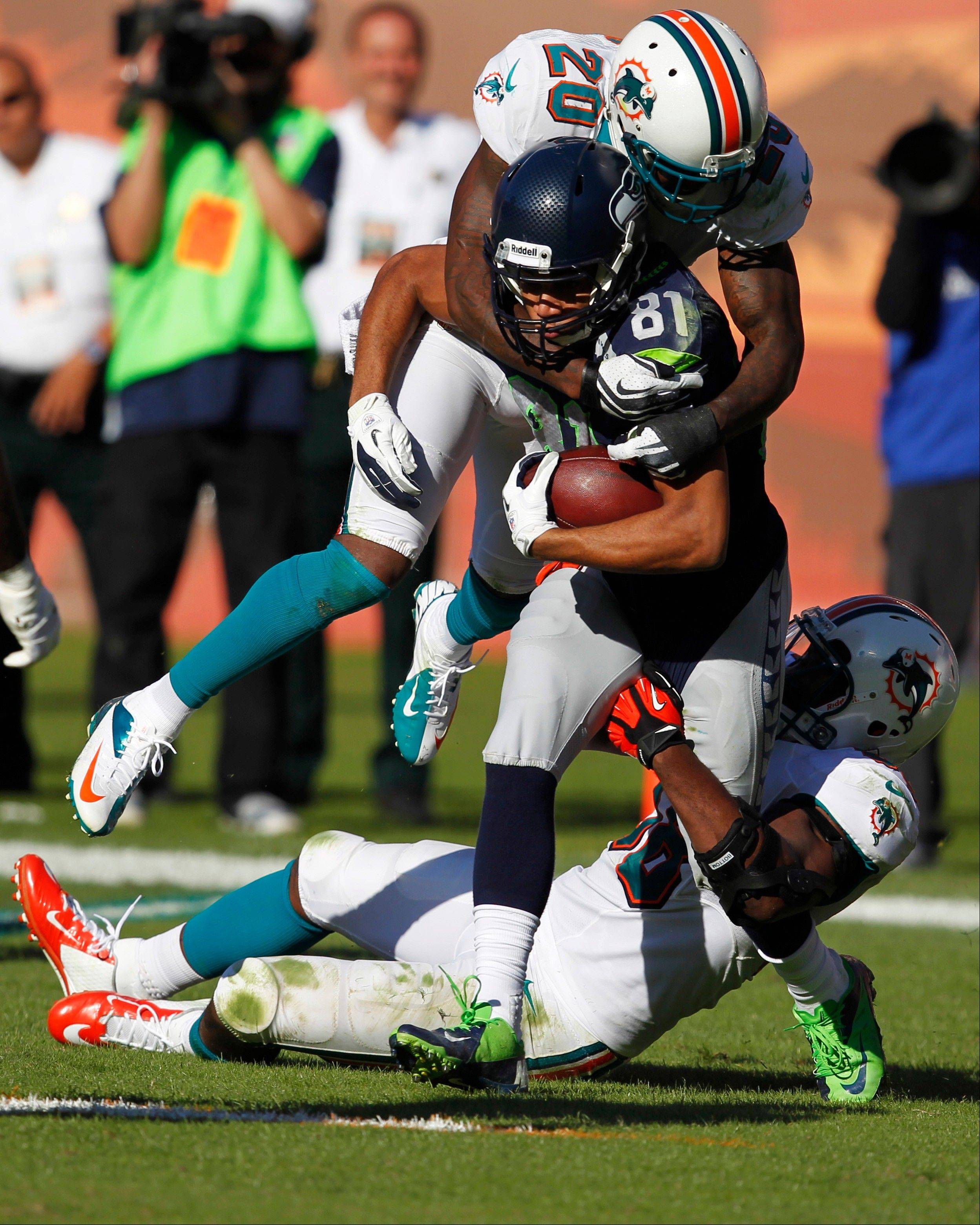 Seahawks wide receiver Golden Tate (81) is tackled by free safety Reshad Jones (20) and linebacker Kevin Burnett (56 )during the second half of an NFL football game Sunday, Nov. 25, 2012 in Miami.