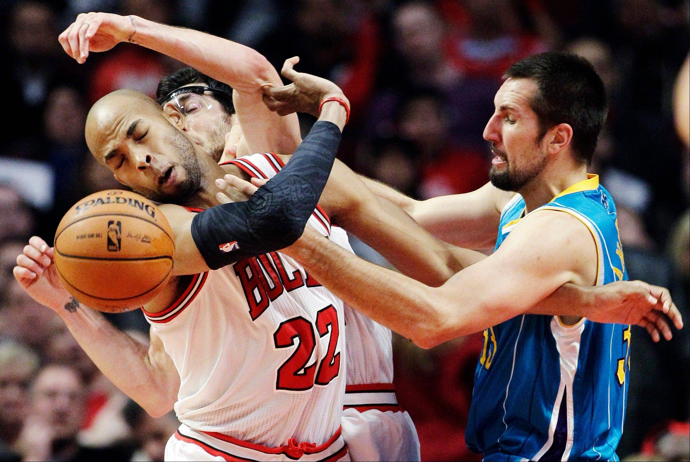 New Orleans Hornets forward Ryan Anderson, right, and Chicago Bulls forward Taj Gibson (22) and guard Kirk Hinrich (12) battle for a rebound during the first half of an NBA basketball game in Chicago, Saturday, Nov. 3, 2012.