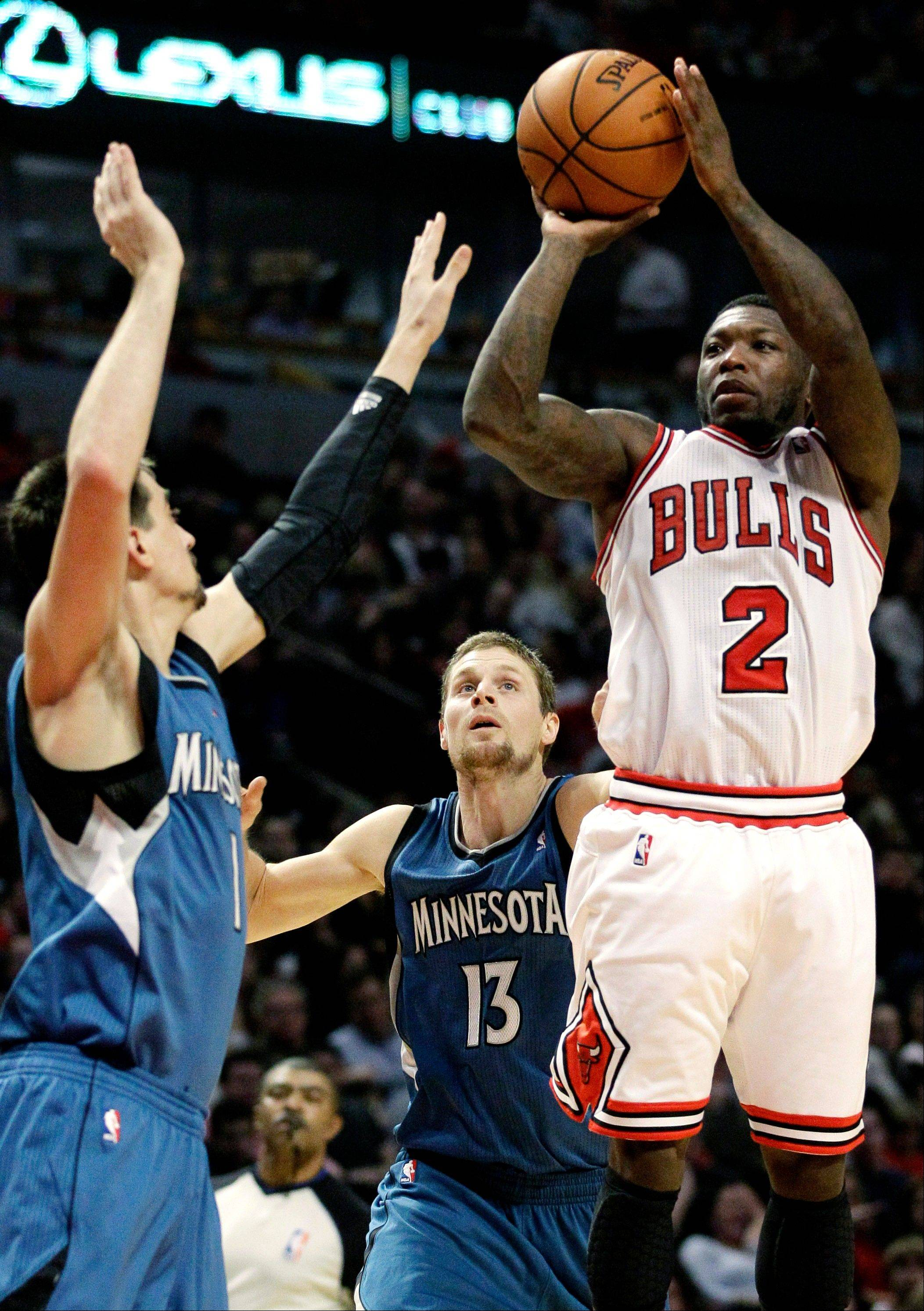 Chicago Bulls guard Nate Robinson (2) shoots against Minnesota Timberwolves guard Alexey Shved, left, and guard Luke Ridnour (13) during the second half of an NBA basketball game in Chicago on Saturday, Nov. 10, 2012. The Bulls won 87-80.
