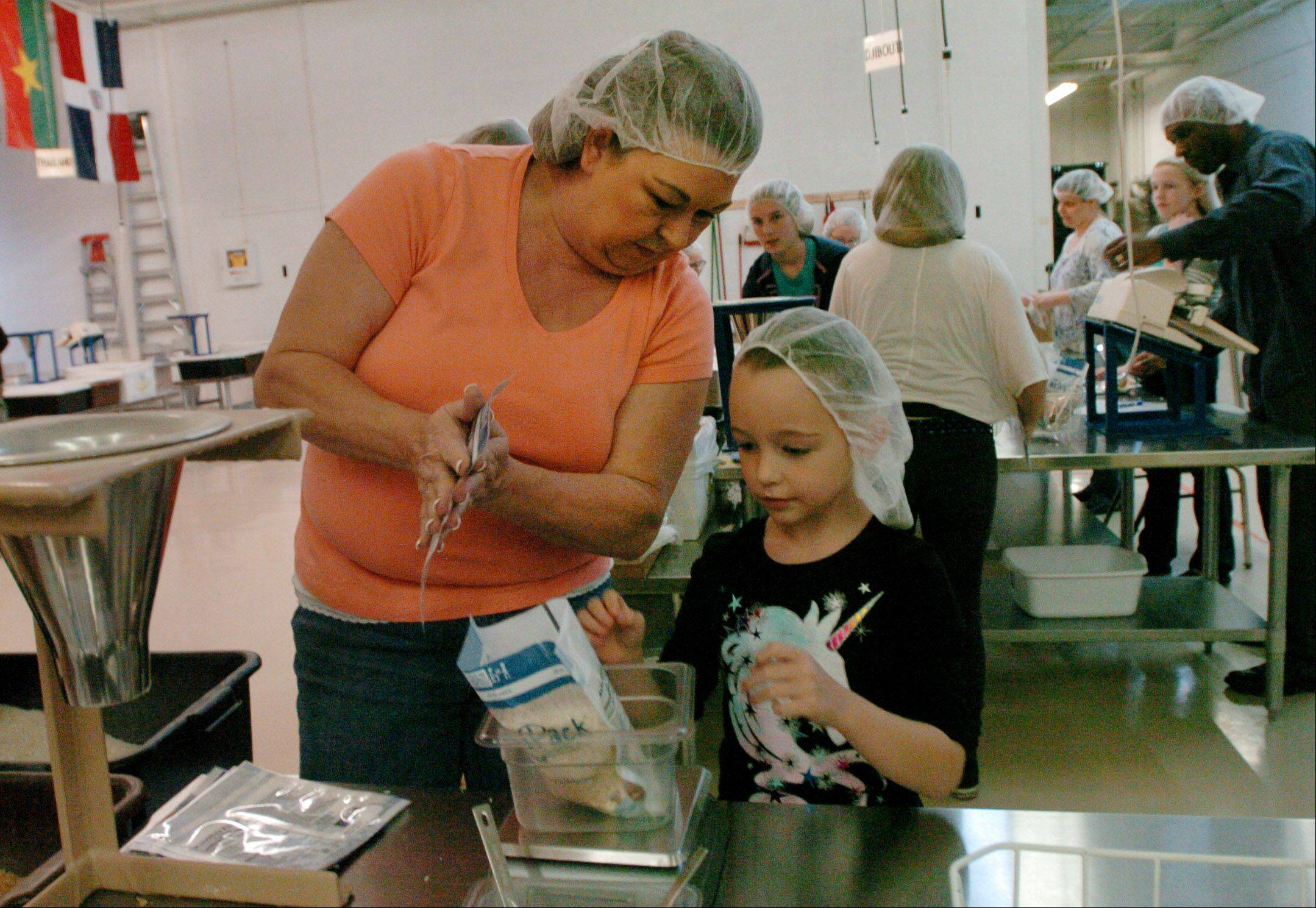 It�s often a family affair at the various locations for Feed My Starving Children, which sends pre-packed meals to hungry children across the globe. Here at the Schaumburg location, home school mother Layna Owens of Elgin packs food with her daughter, Joah Owens, along with the Fox Valley Home Schoolers.