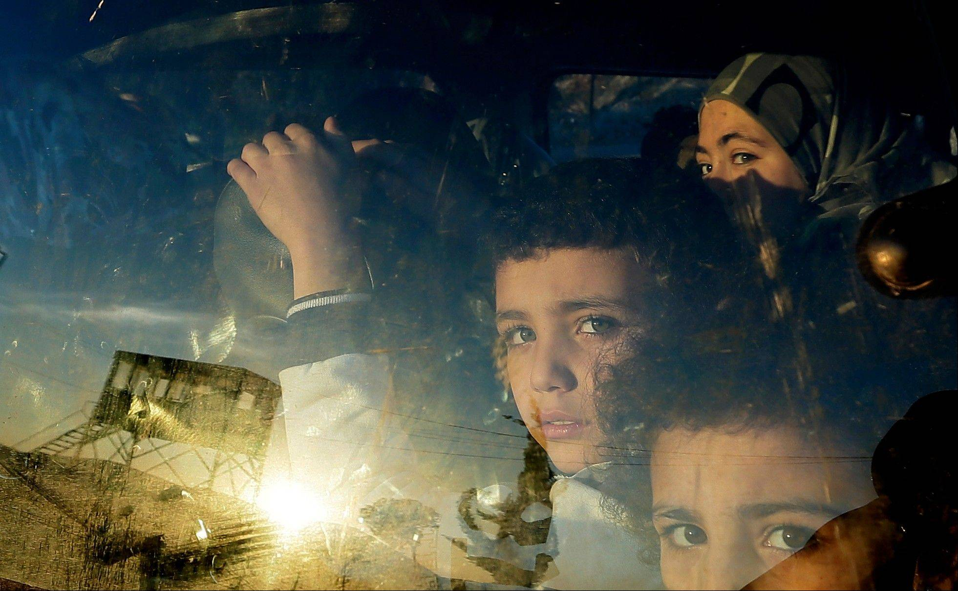 Associated Press Syrian children look through their car window Friday as they cross into Lebanon with their families at the border crossing, in Masnaa, eastern Lebanon.