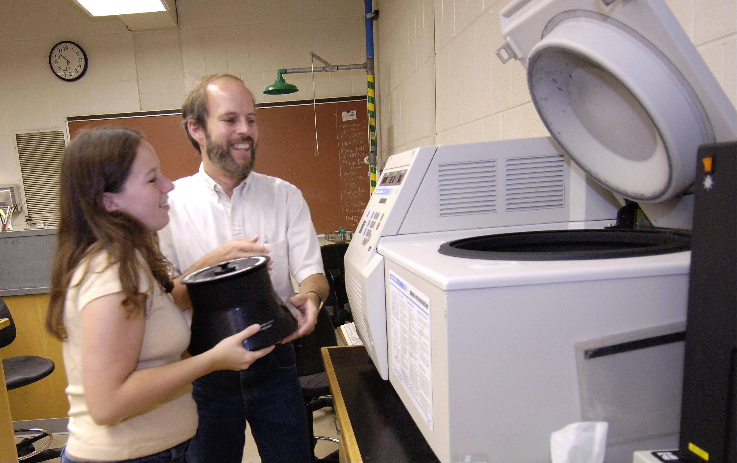 Daily Herald/2005 NCC junior Nicole Flinn, left, and Jon Visick, Assistant Biology Professor, lift a rotor into a Centrifuge in the Genetics & Microbiology lab at the Science Center in Naperville.