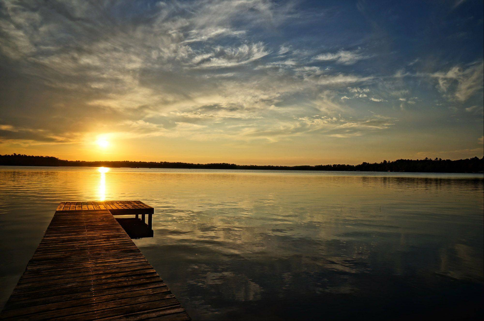 The sun sets over a dock during the summer in Conover, Wisconsin.