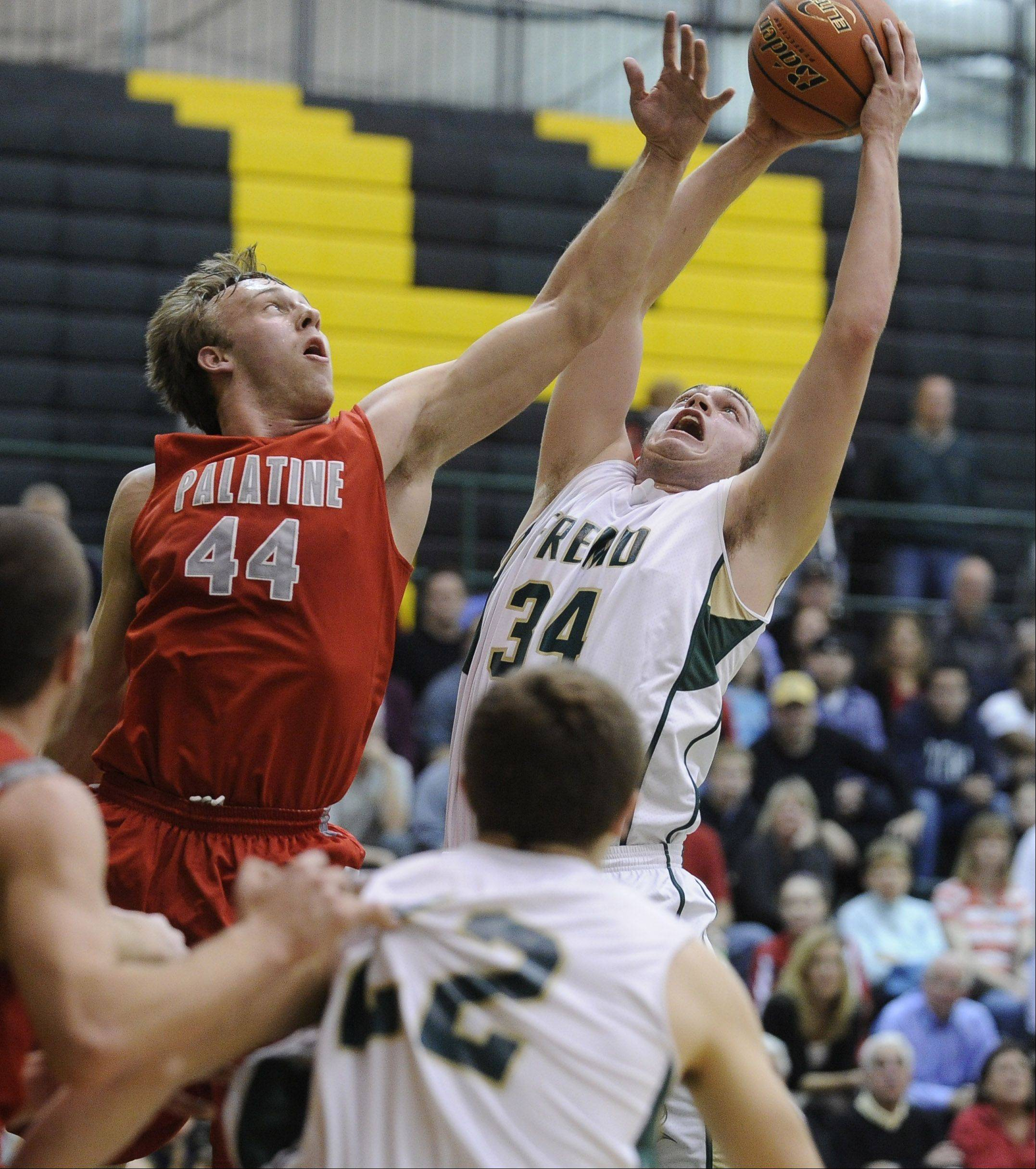 Palatine�s Josh Baldus, left, and Fremd�s Ben Carlson battle for the rebound in the first half Friday at Fremd.