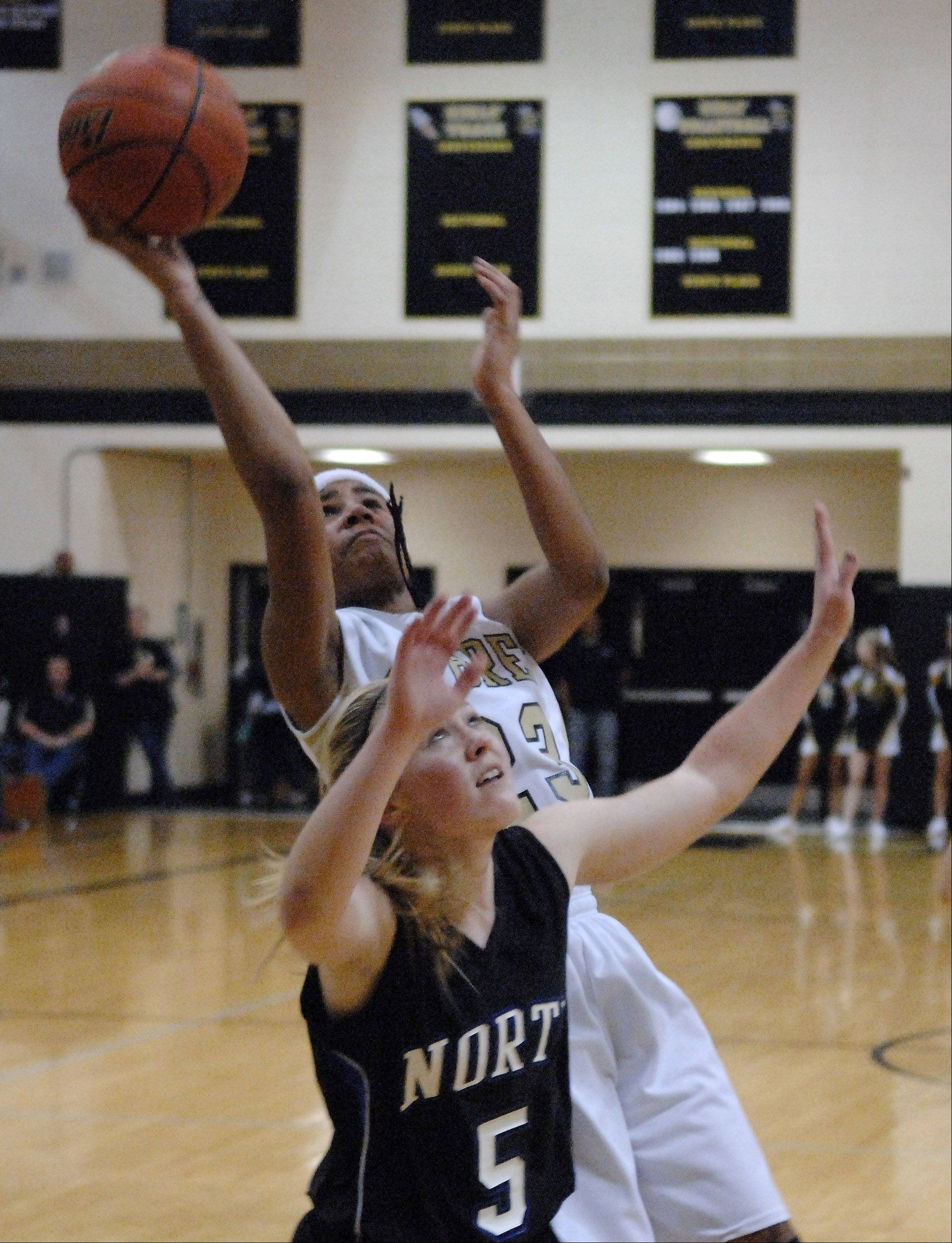 Streamwood�s Deja Moore puts up a shot over St. Charles North�s Natalie Winkates after grabbing an offensive rebound during Friday�s game at Streamwood.