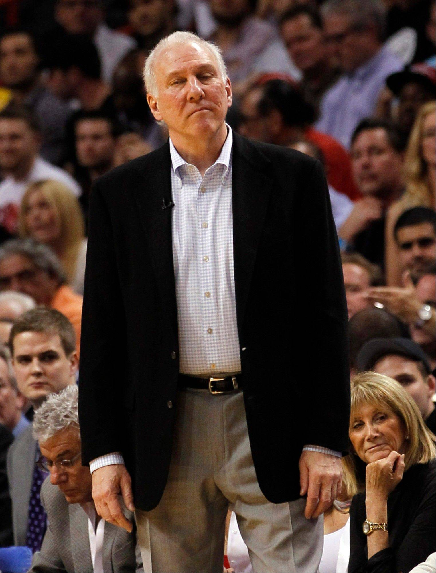 San Antonio Spurs head coach Gregg Popovich watches from the sideline Thursday during the second half against the Miami Heat in Miami. The NBA fined the Spurs $250,000 on Friday for sending four players home Thursday before their game against the Heat.