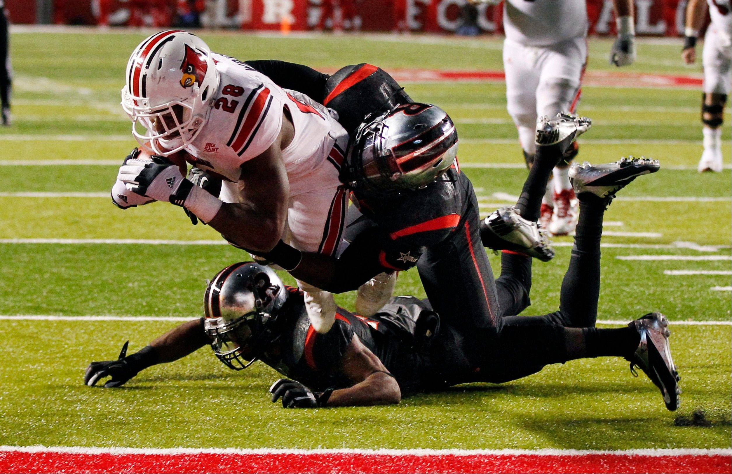 Louisville running back Jeremy Wright (28) dives over Rutgers defenders for a touchdown during the second half of an NCAA college football game in Piscataway, N.J., Thursday, Nov. 29, 2012. Louisville won 20-17. (AP Photo/Mel Evans)