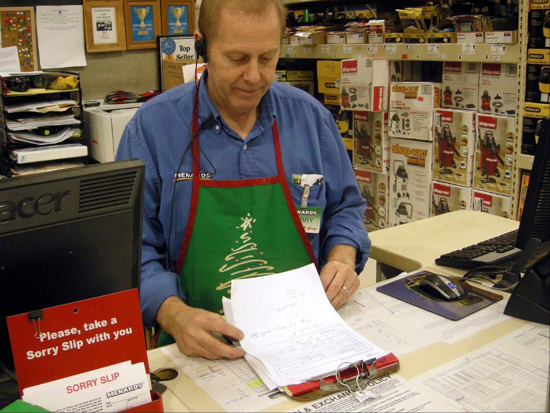 Larry Boutilier, hardware manager, who has been with the Minot, N.D. Menards since 1996, looks over paperwork at the storey in Thursday. The home improvement retailer says it will hire workers from its home base in Wisconsin and fly them to North Dakota to staff a store in Minot, which is near the state's booming oil patch and has more jobs than takers.