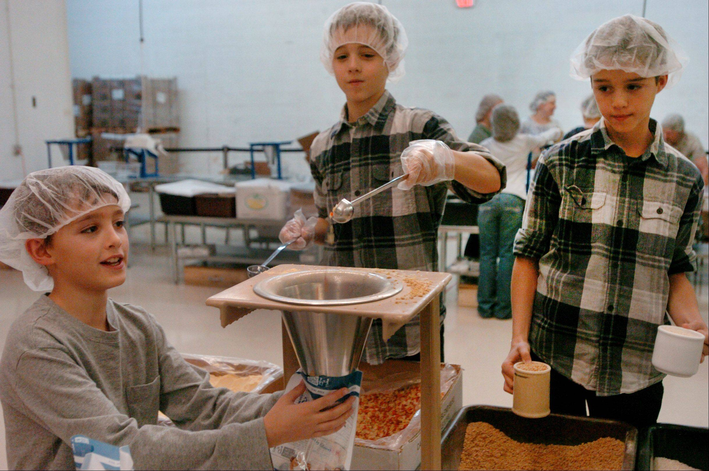 Families from the Fox Valley Home Schoolers worked together recently at the Feed My Starving Children location in Schaumburg. Pictured, from left, are Kenton Weiss of Huntley, and Quinn and Kyle Schieler of Elgin.