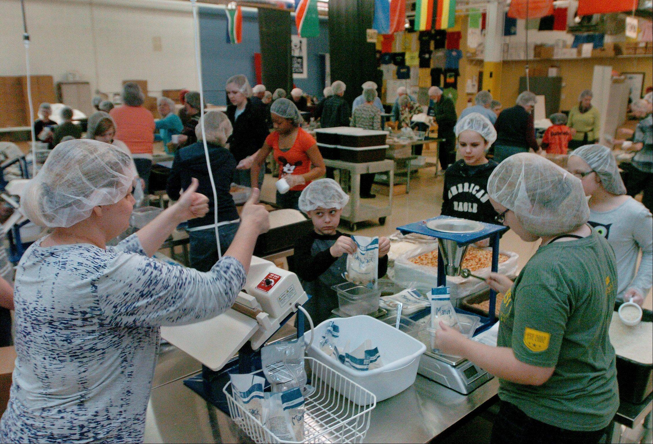 Sara Green of Elgin, left, gives a thumbs-up to her kids from left, Elijah, Emma, Hannah Green, along with Jessica Owens, while packing food at Feed My Starving Children in Schaumburg with the Fox Valley Home Schoolers.