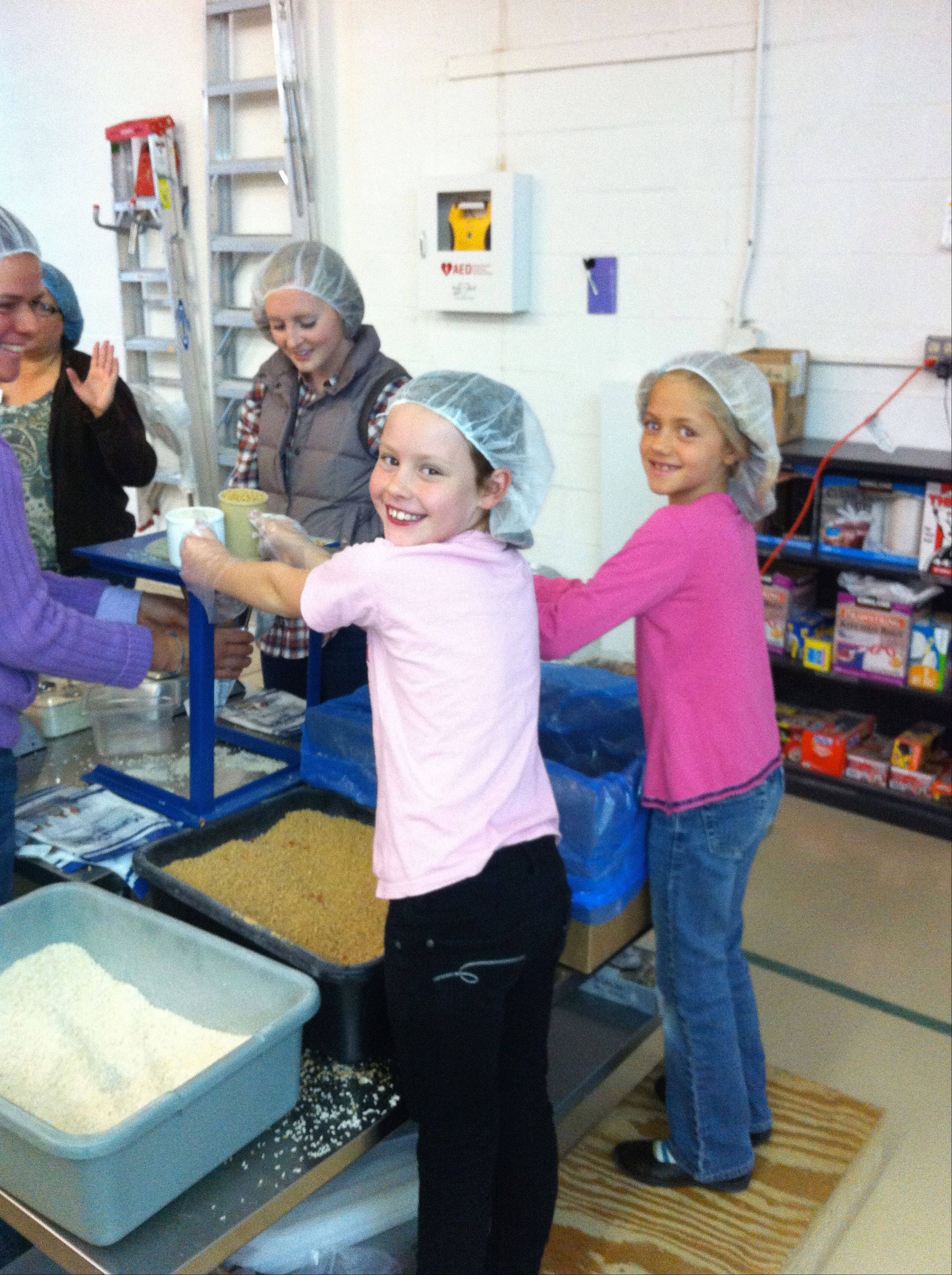 Madeline Handrich, left, and her friend, Laurie Taranowski, both 9, joined their families in filling food bags for Feed My Starving Children when the charity set up a mobile event at East Lake Academy in Lake Forest last spring.