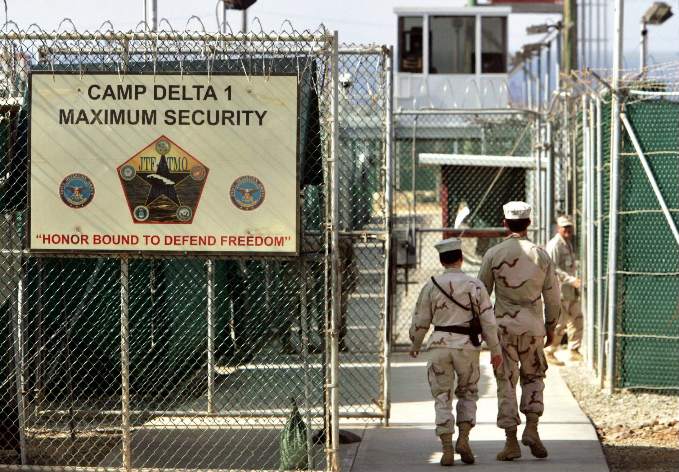 U.S. military guards walk within Camp Delta military-run prison, at the Guantanamo Bay U.S. Naval Base, Cuba. The White House is threatening that President Barack Obama would veto the defense bill unless Congress makes changes.