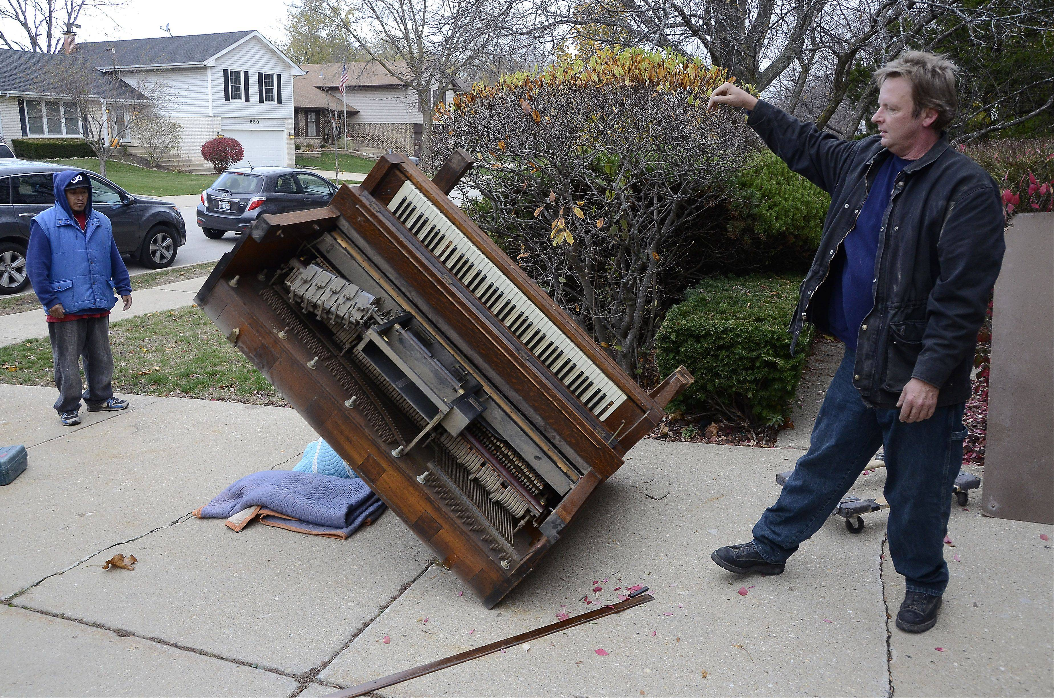 Glen Hansen lets a player piano fall in the driveway of a Schaumburg home as his helper, Mauro Pugo, looks on. The impact will help loosen glue joints making demolition easier. Hansen works for Art's Junk Removal in Mount Prospect.
