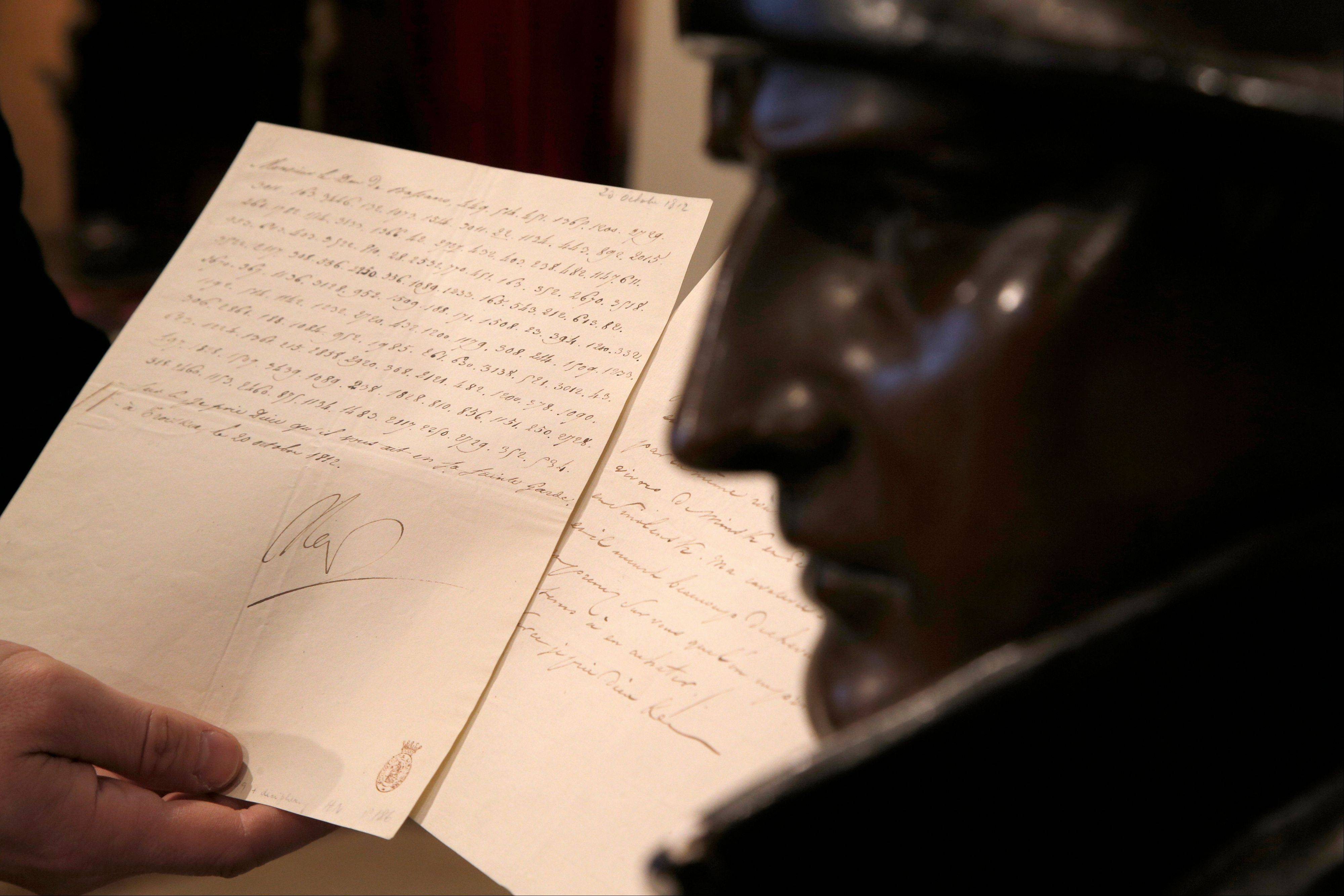 "A letter dictated and signed by Napoleon in secret code that declares his intentions ""to blow up the Kremlin"" during his ill-fated Russian campaign is displayed for the media in Fontainebleau, outside Paris. The rare letter, written in unusually emotive language, sees Napoleon complain of harsh conditions and the shortcomings of his grand army. The letter goes on auction Sunday, Dec. 2, 2012."