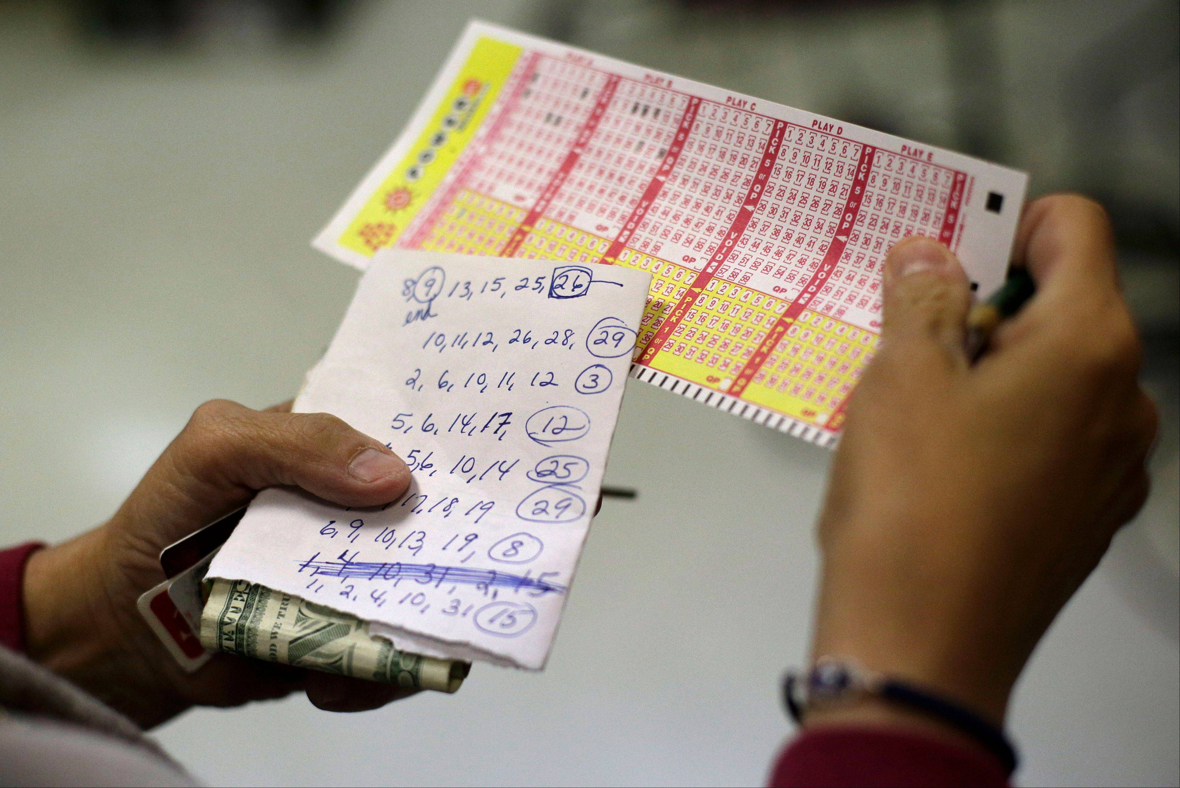 Sharon Long double checks her Powerball numbers Wednesday as she stands in line in a convenience store in Baltimore. Long picked numbers that her sister asked her to play.