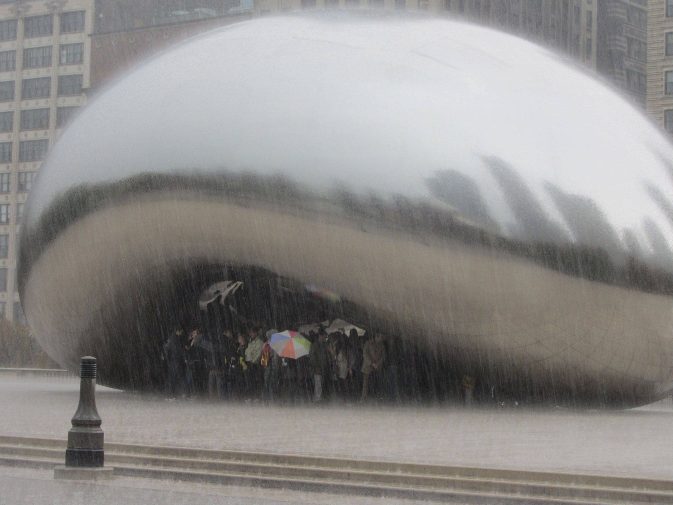 As the rain turned to a downpour, most visitors who came to see The Bean at Millennium Park in downtown Chicago were caught without umbrellas earlier this month. The all huddled under The Bean and waited for the thunderstorm to pass.