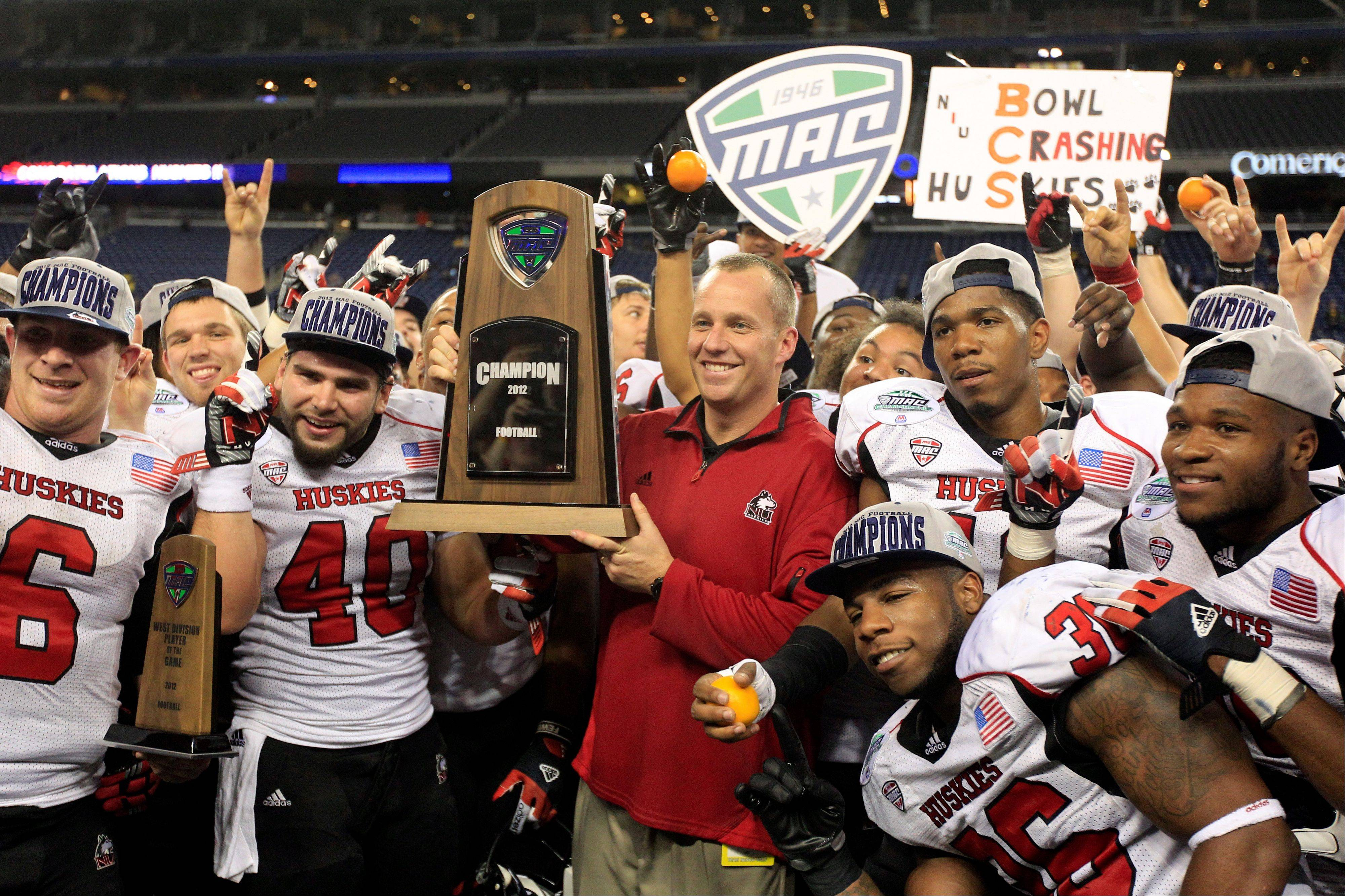 Northern Illinois head coach Dave Doeren, center, holds the Mid-American Conference championship trophy Friday after defeating Kent State 44-37 in double overtime at Ford Field in Detroit.