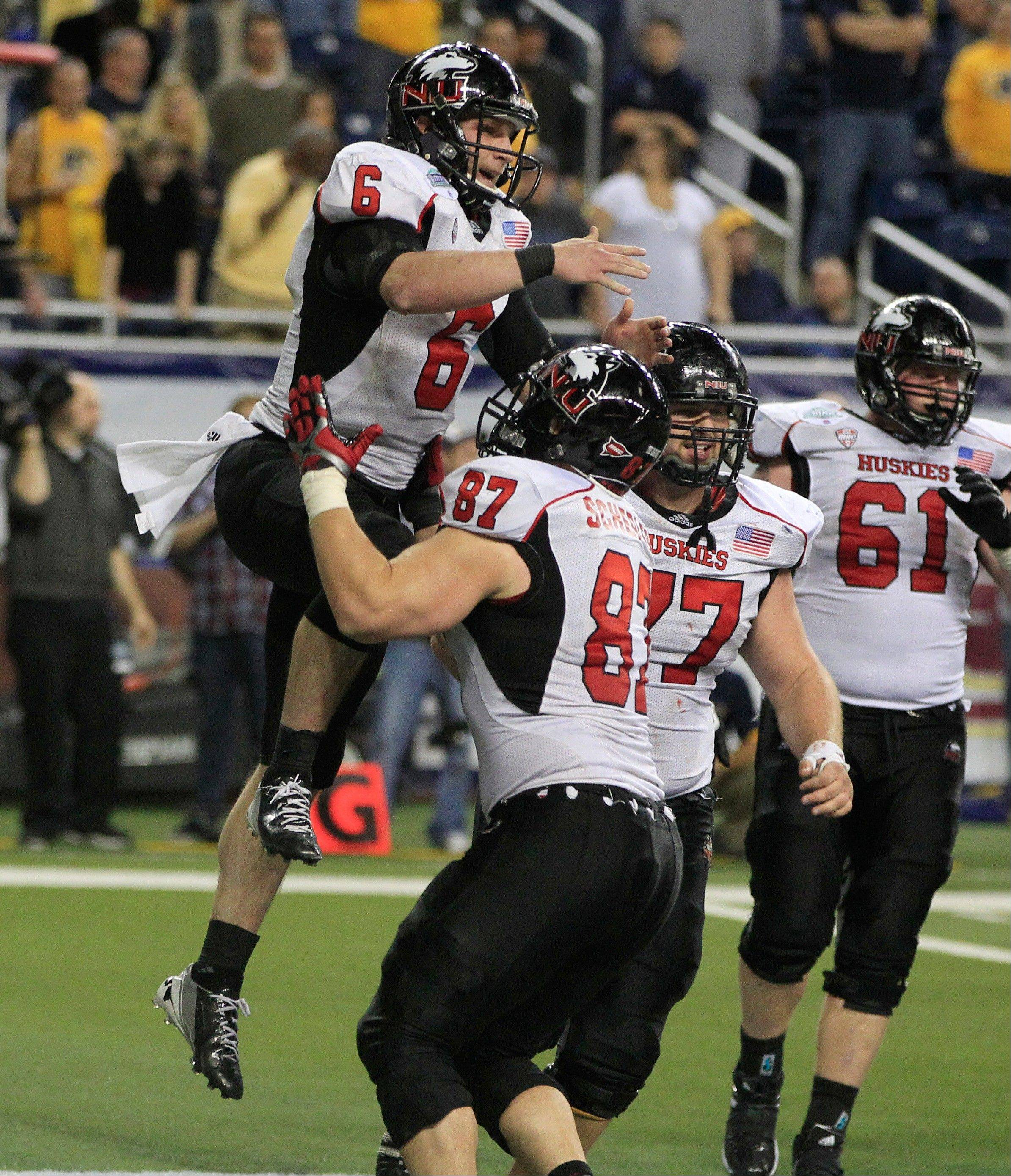 Northern Illinois quarterback Jordan Lynch (6) jumps onto teammate Jason Schepler after scoring a touchdown Friday during the second overtime.