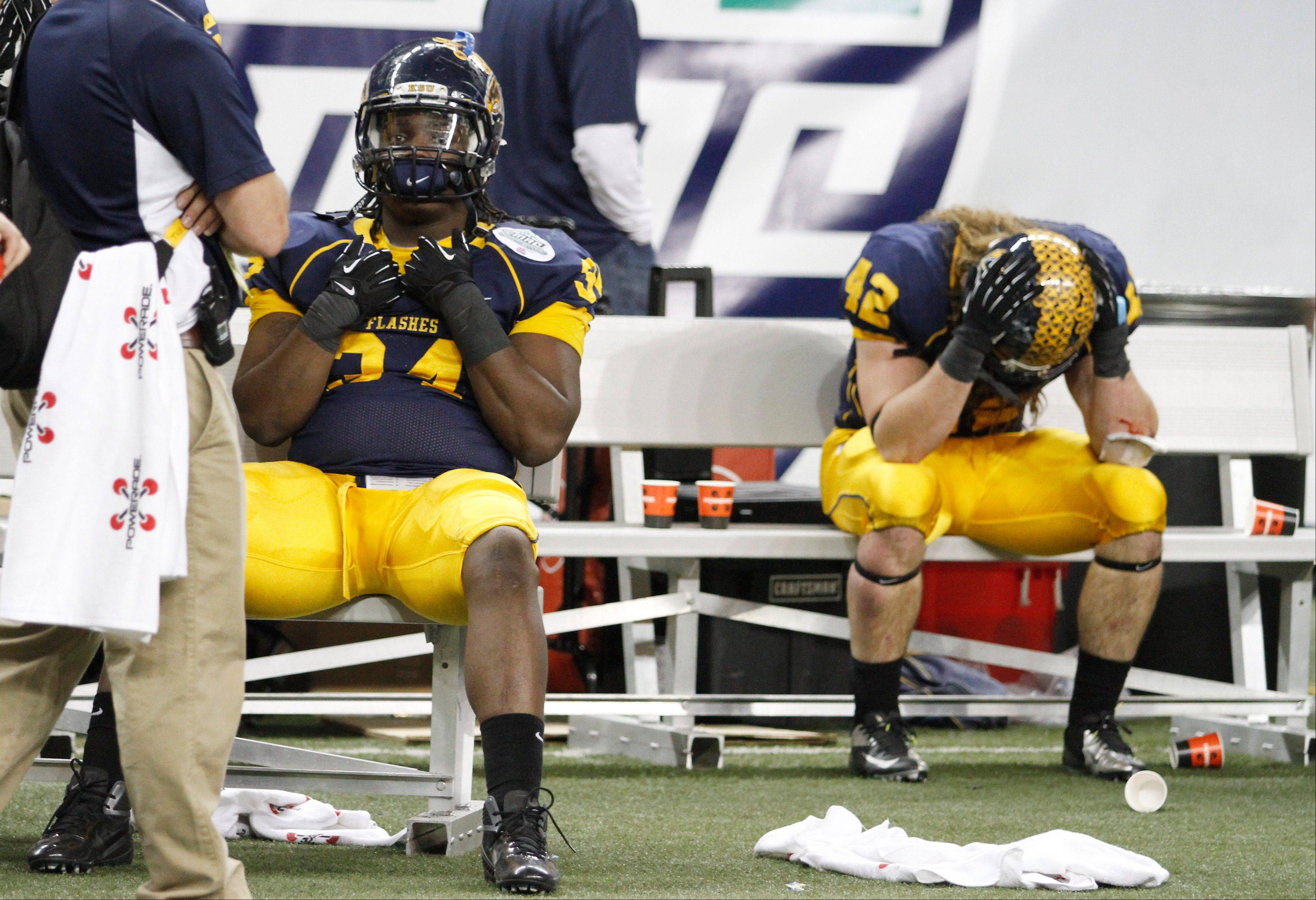 Kent State defensive lineman Richard Gray (34) and tight end Tim Erjavec (42) sit on the bench Friday after losing to Northern Illinois 44-37 in double overtime.