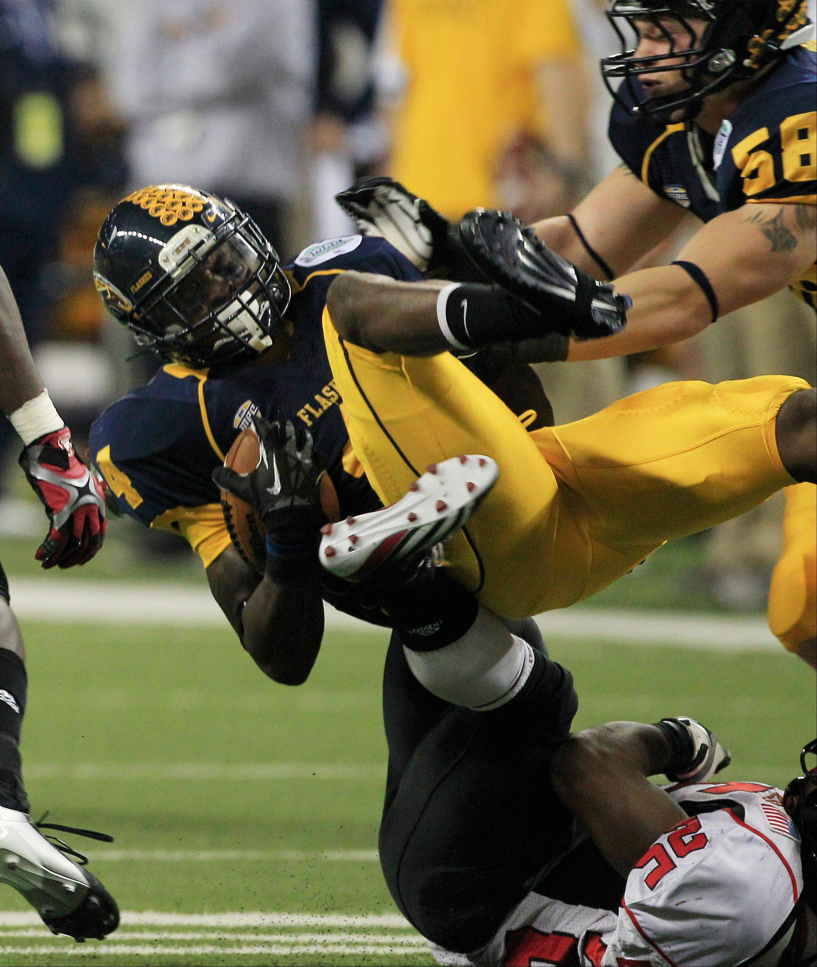 Kent State wide receiver Eric Adeyemi is upended by Northern Illinois' Giorgio Bowers Friday.