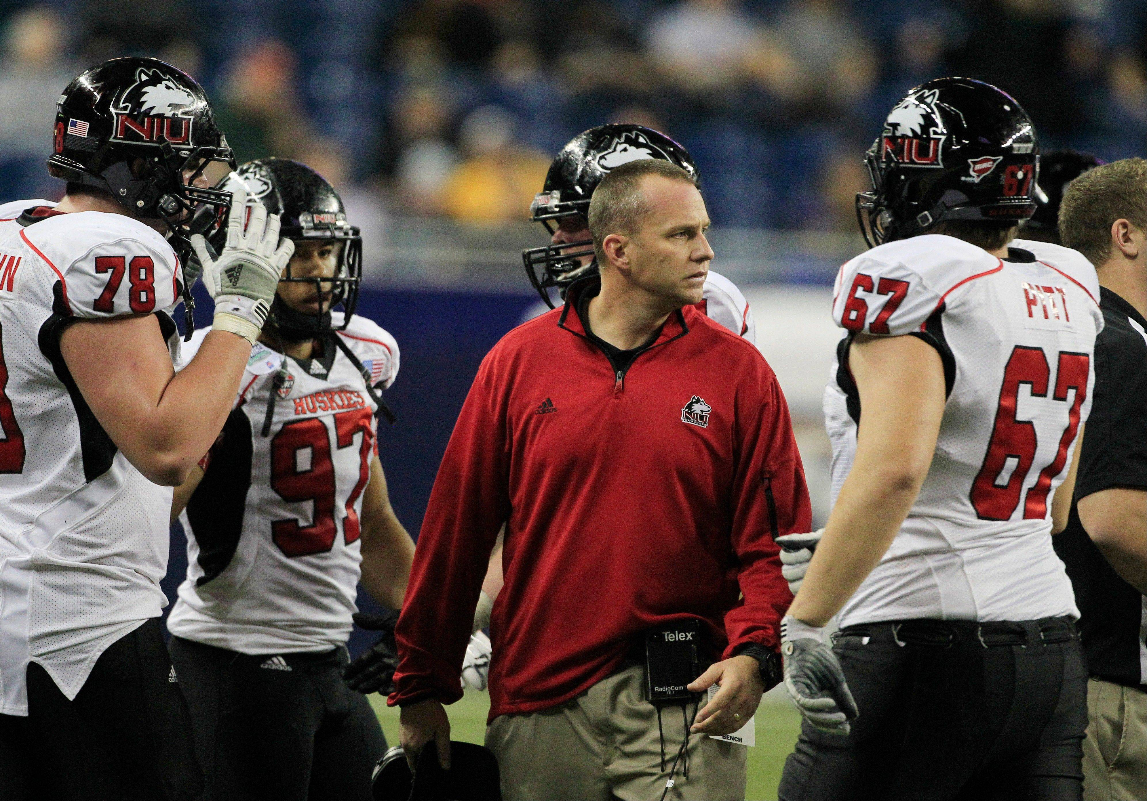 Northern Illinois head coach Dave Doeren, center, prepares to talk to his team Friday during the third quarter.