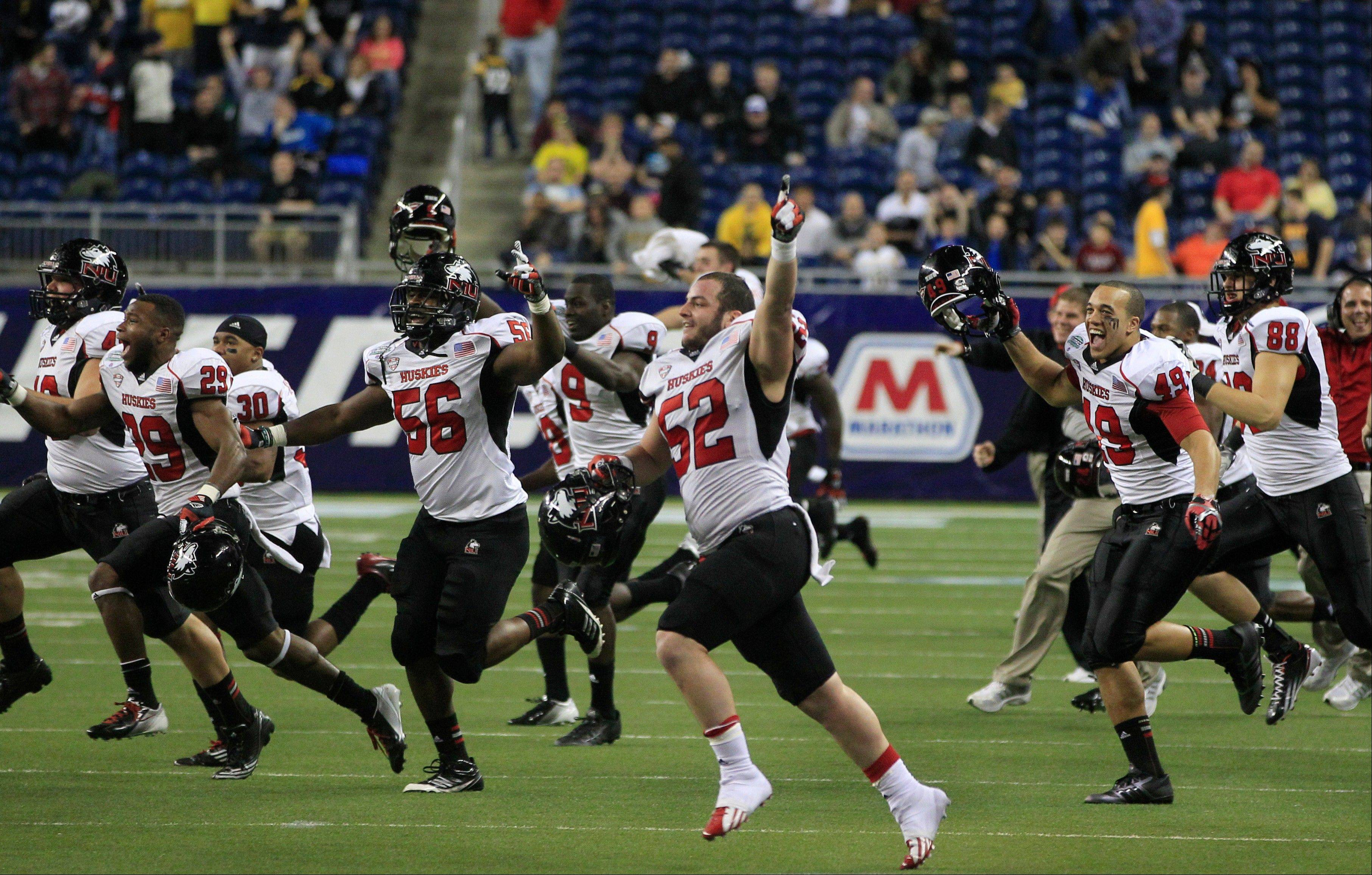 The Northern Illinois team rushes the field after their 44-37 double OT win Friday over Kent State.
