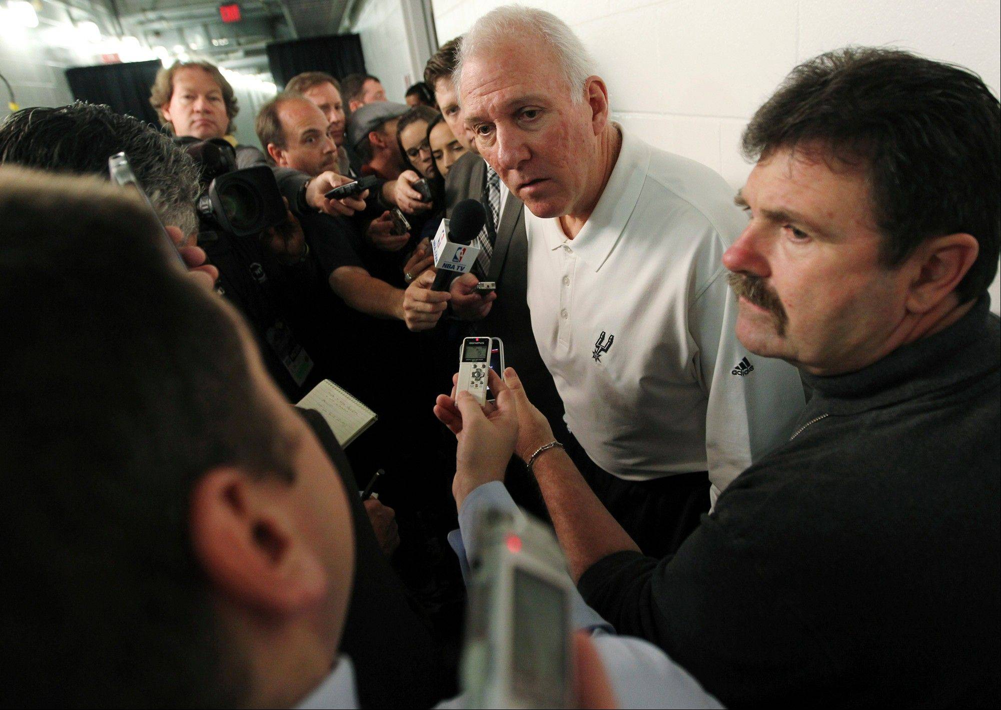 San Antonio Spurs head coach Gregg Popovich speaks to reporters Thrusday before the game against the Miami Heat in Miami. Commissioner David Stern said the Spurs will be punished by the league for their decision to send Tim Duncan, Tony Parker, Manu Ginobili and Danny Green home and not make them available to play against the Heat.