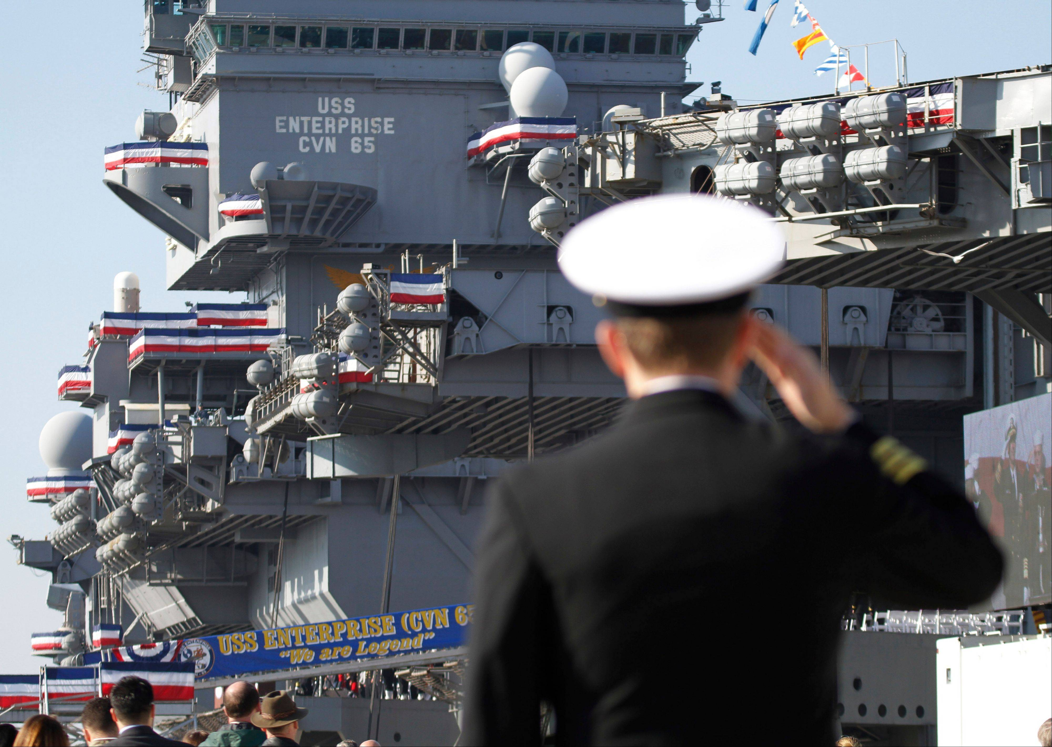A Navy officer salutes Saturday during the inactivation ceremony for the first nuclear powered aircraft carrier USS Enterprise at Naval Station Norfolk in Norfolk, Va. The ship served in the fleet for 51 years.