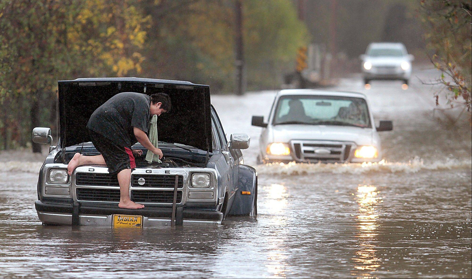 Milton Lopez of Windsor, Calif., attempted to drive through flood waters on Mark West Station Road Friday at Starr Road in Windsor, Calif.