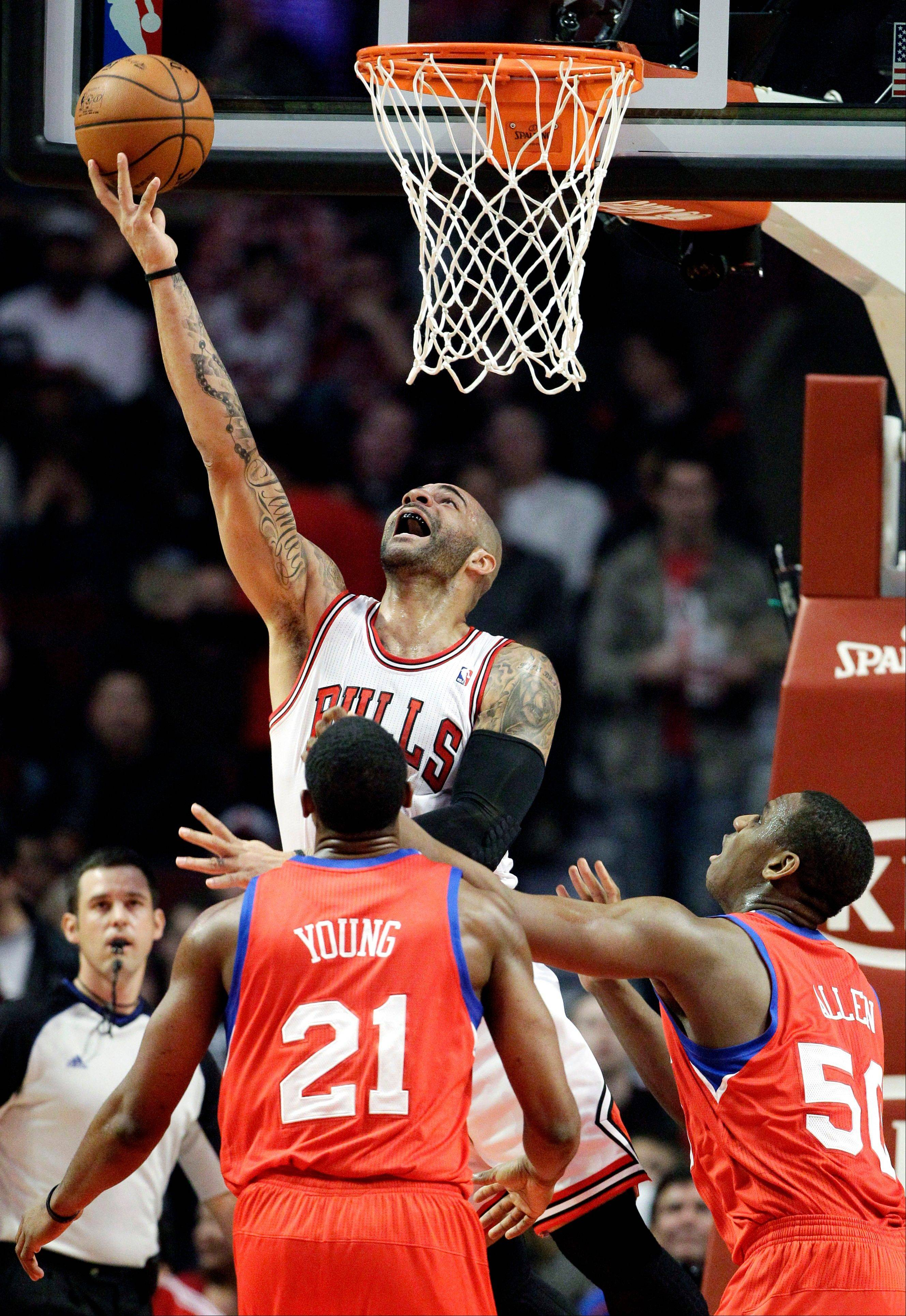 Bulls forward Carlos Boozer, top, shoots as Philadelphia 76ers forward Thaddeus Young (21) and center Lavoy Allen (50) look on Saturday during the first half.