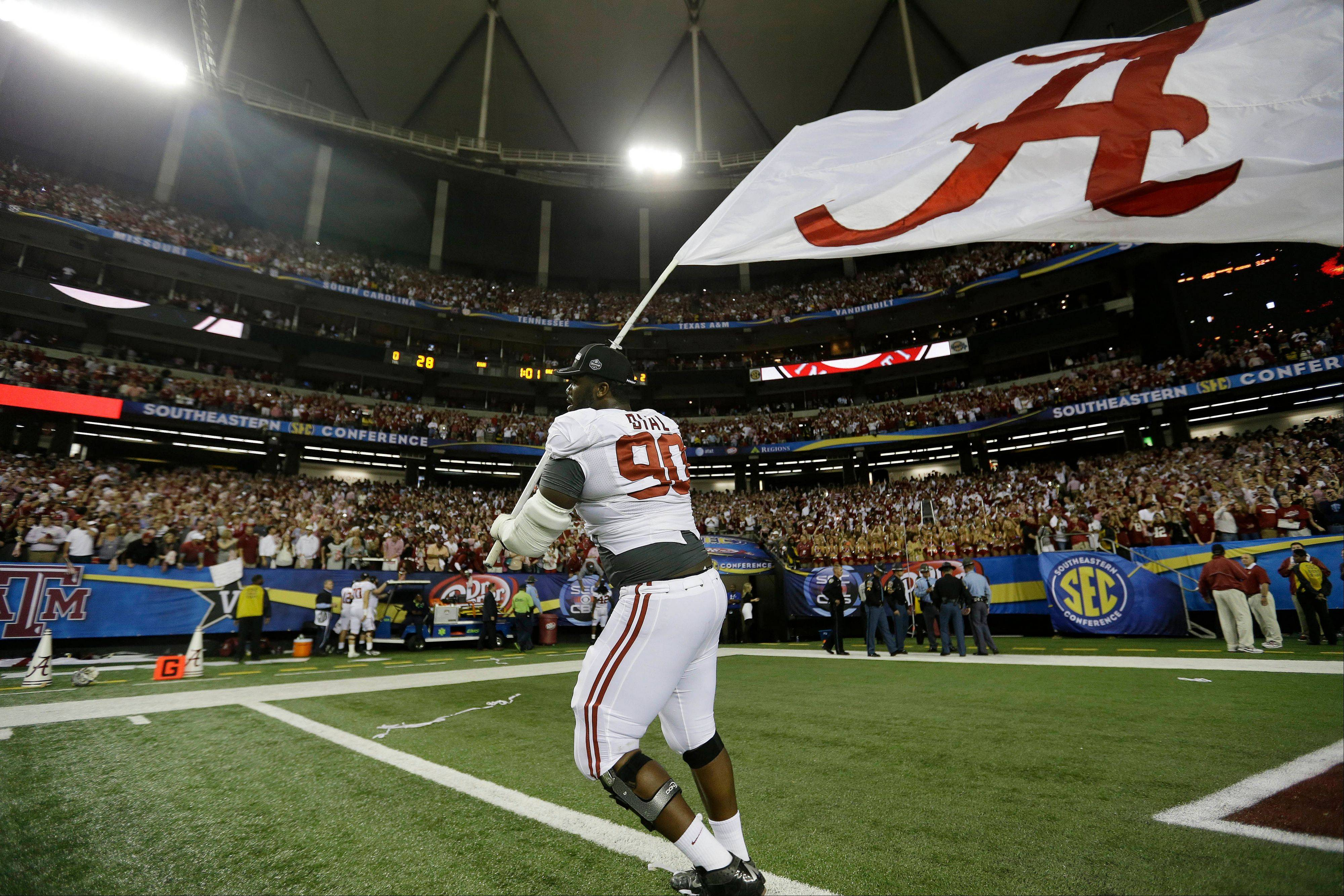 Alabama defensive lineman Quinton Dial runs on the field with a Alabama flag Saturday after their 32-28 win in the Southeastern Conference championship against Georgia in Atlanta.