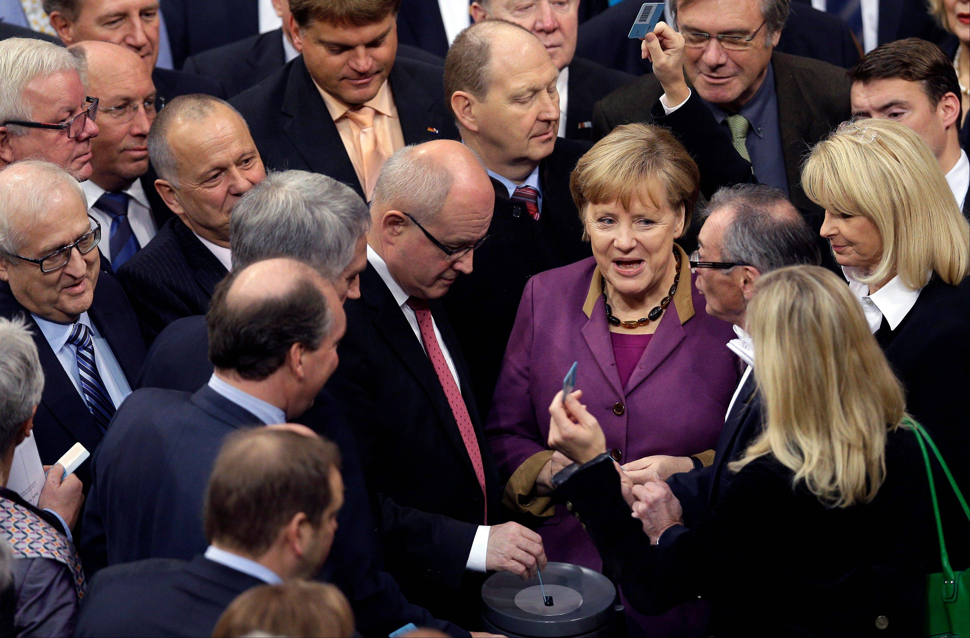 German Chancellor Angela Merkel casts her vote Friday at the German federal parliament, Bundestag, in Berlin, Germany. The German Parliament has given its overwhelming backing to a deal aimed at trimming Greece's debt load and keeping the country financially afloat.