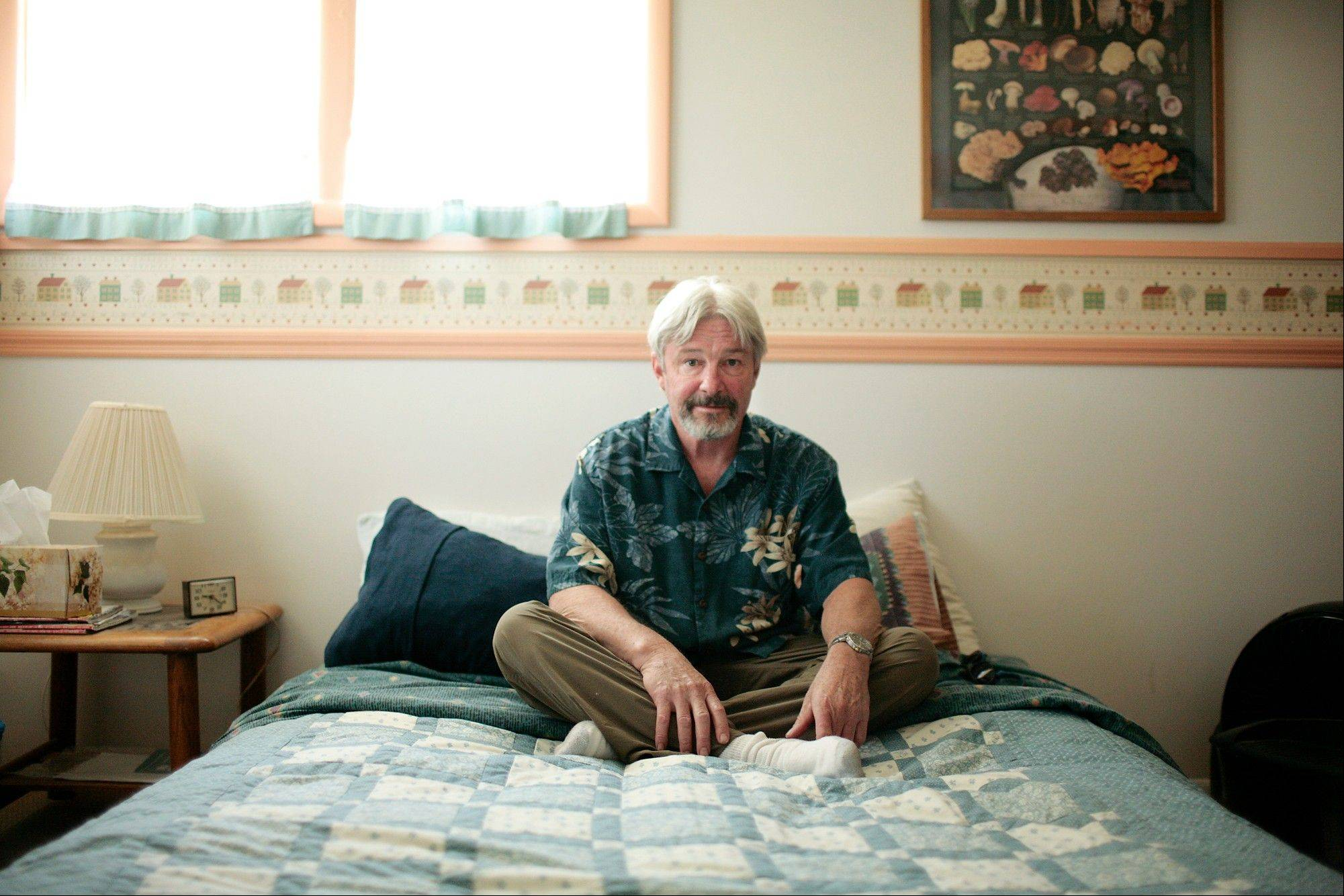 Don Killian sits on the bed he offers up to strangers at no cost in Bozeman, Mont. Killian is one of the 150 Bozeman, Mont., members of CouchSurfing.org, a website for travelers looking for a free place to stay.