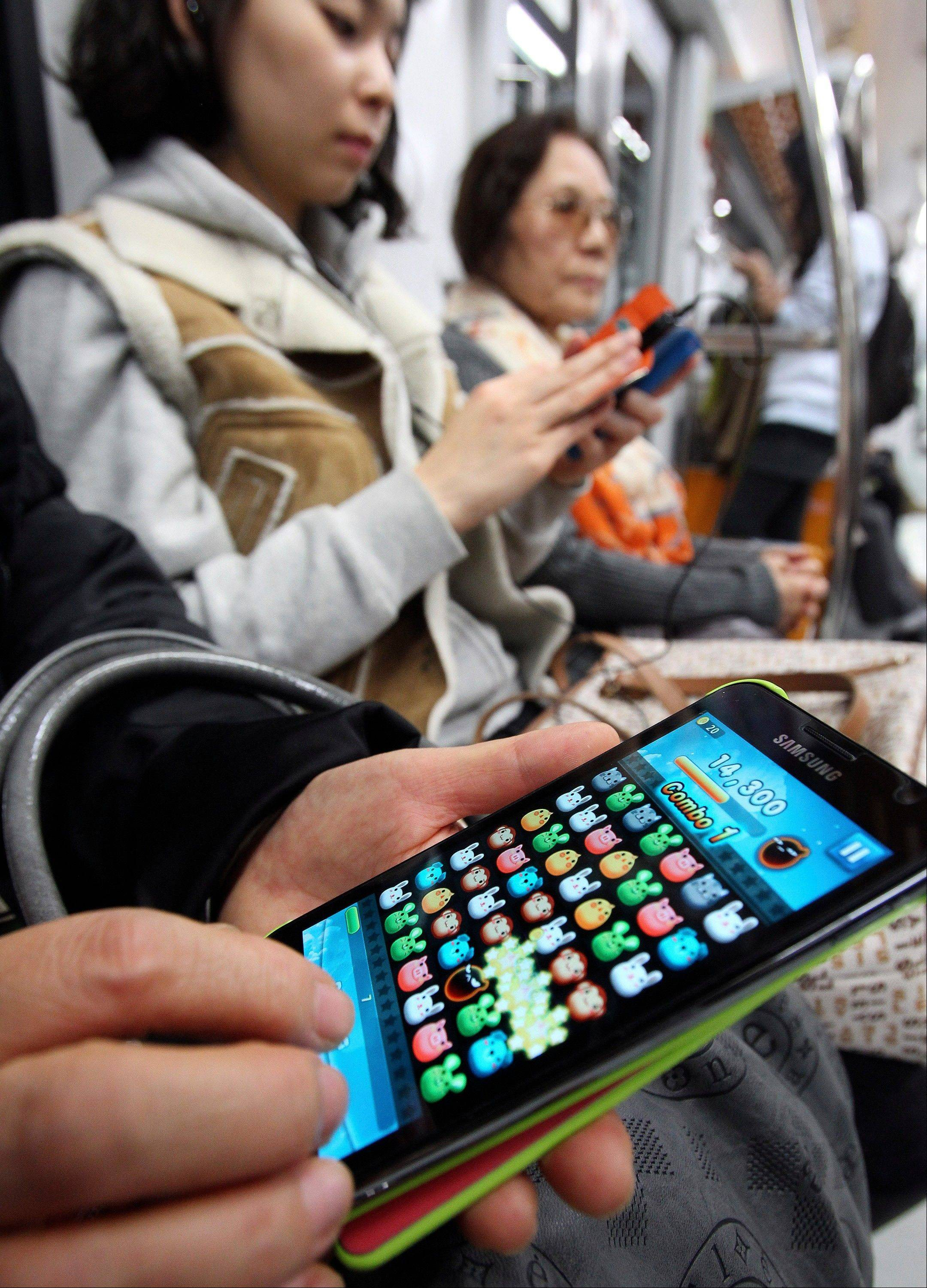 A passenger plays a game with a smartphone on a subway in Seoul, South Korea. Across the entire population, South Korea's government estimated 2.55 million people are addicted to smartphones, using the devices for 8 hours a day or more, in its first survey of smartphone addiction released earlier this year.