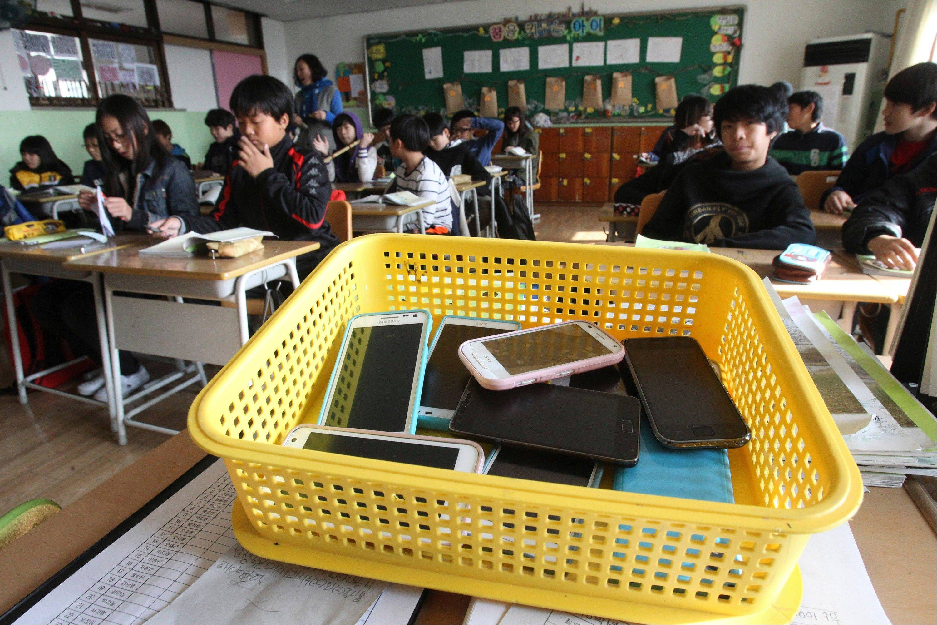 Smartphones collected from students are placed in a plastic basket during a class at Chilbo elementary school in Suwon, South Korea. Students agreed to hand in their smartphones when they arrive at school in the morning and get them back when they leave for home after classes.