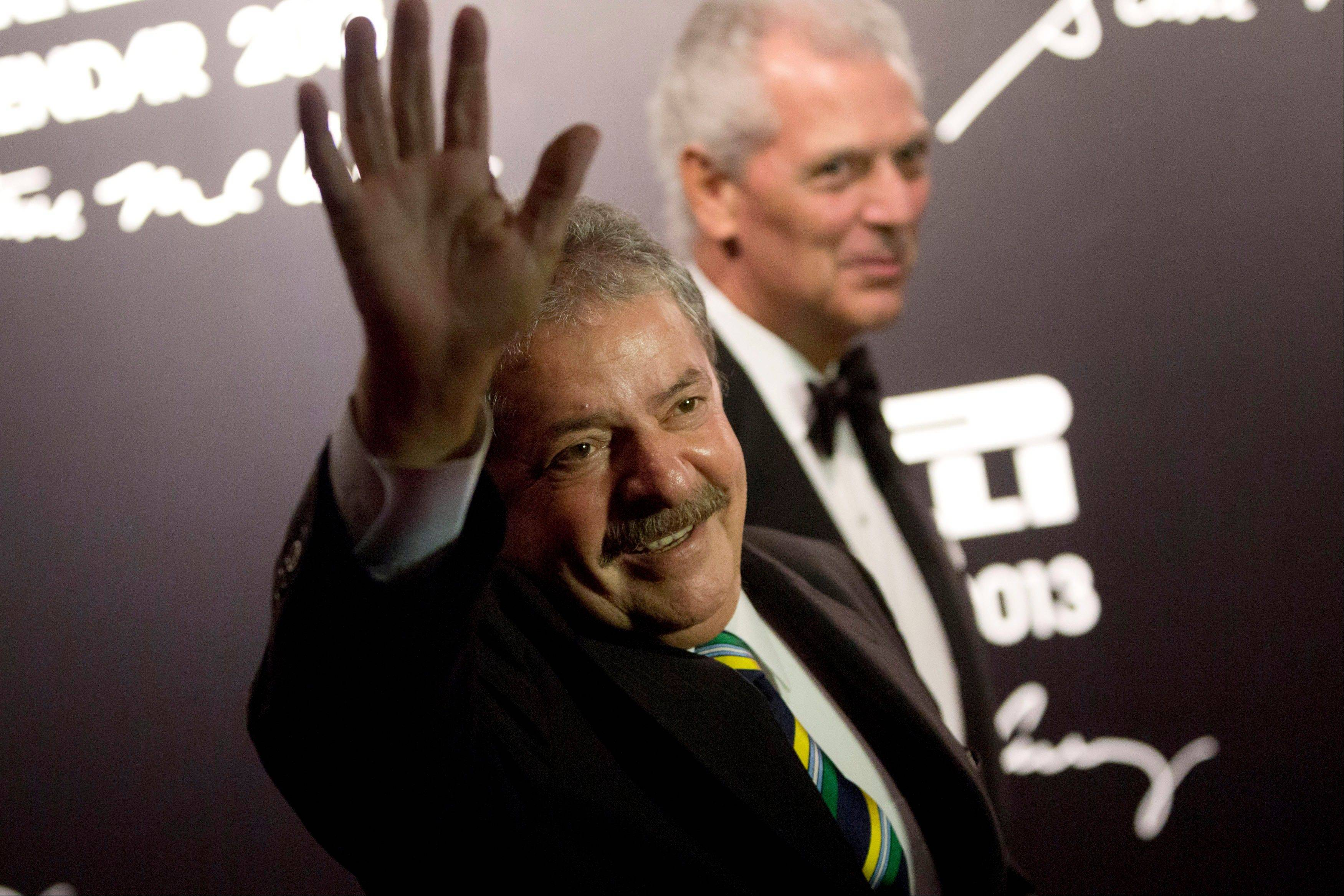 Brazil's former President Luiz Inacio Lula da Silva waves as he stands near Pirelli Chairman Marco Tronchetti Provera at the 2013 Pirelli Calendar red carpet event in Rio de Janeiro, Brazil.