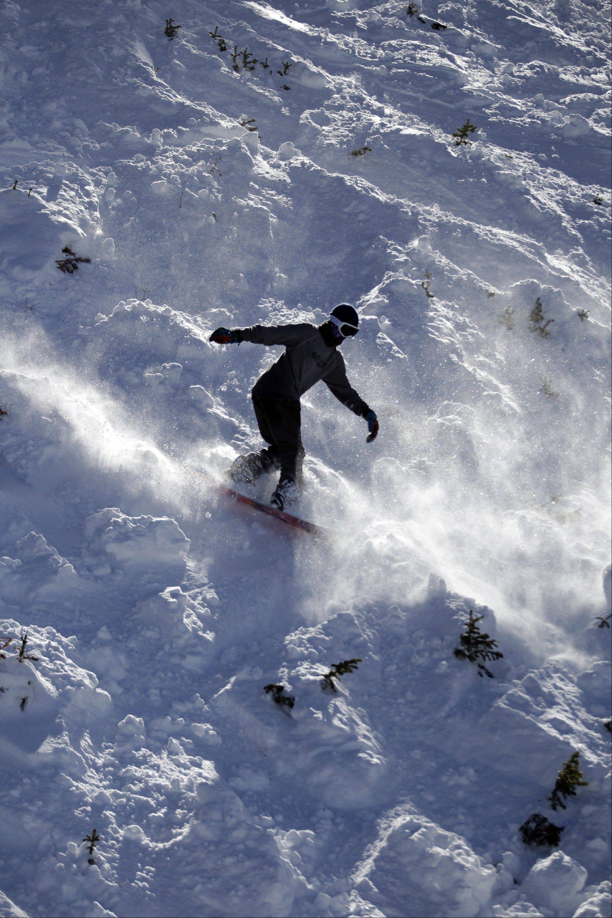 A snowboarder goes down a slope at the Brighton Ski Resort along the Wasatch Range in Utah.