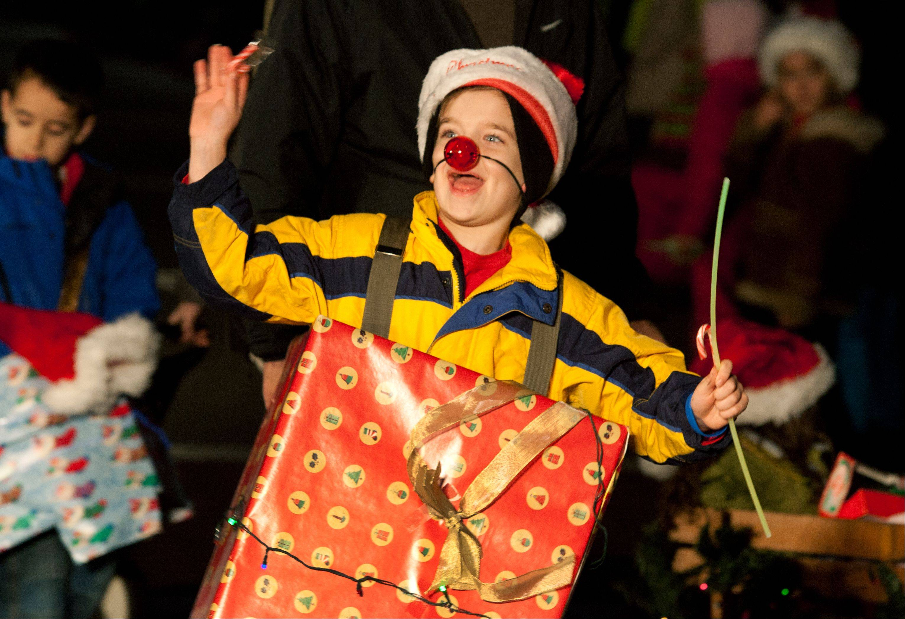 Cub Scout Pack 317's Brian Beutell, along with other members from Patterson School, marches in Saturday's Little Friends Parade of Lights in Naperville.