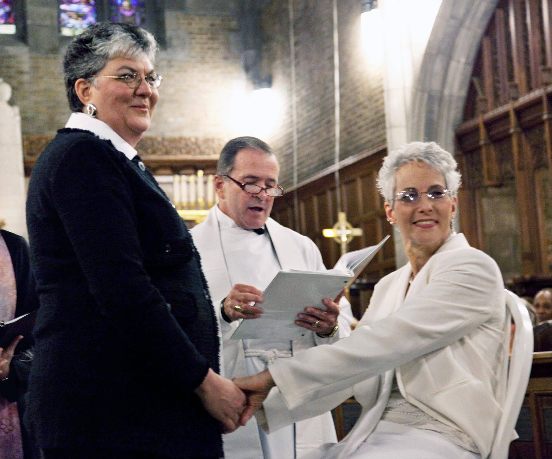 Brenda Sue Fulton, left, and Penelope Gnesin, hold hands Saturday while exchanging wedding vows at the U.S. Military Academy at West Point, N.Y.